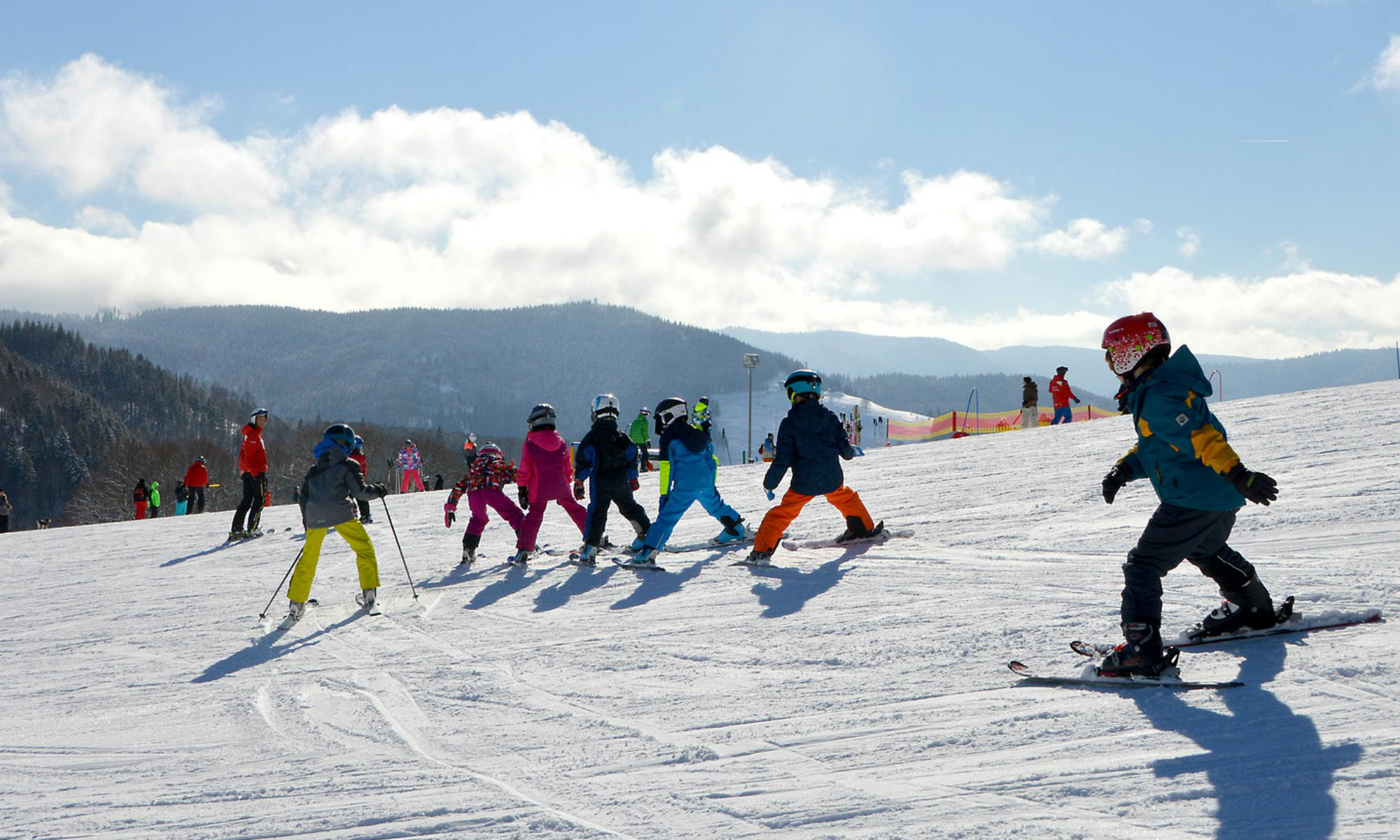Un gruppo di bambini in fila scende la pista sotto la supervisione del maestro di sci.