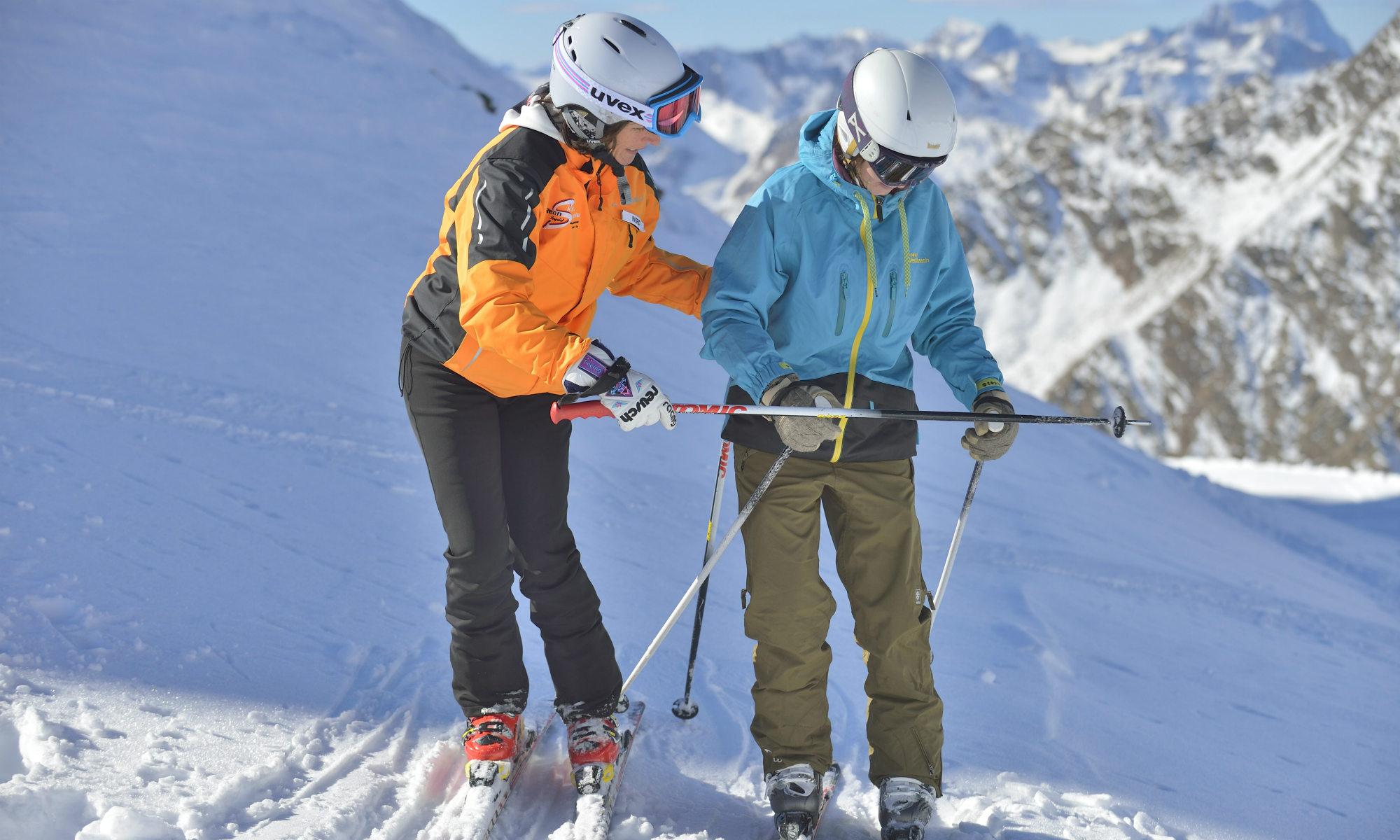 Eine Skilehrerin zeigt einem Skifahrer im Rahmen eines privaten Skikurses die richtige Technik.