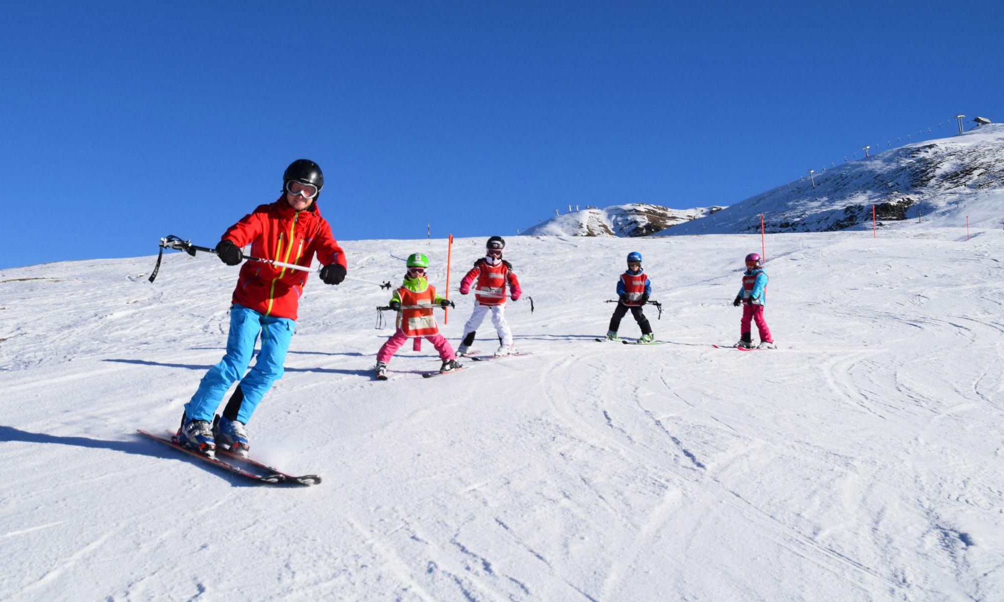 Eine Gruppe Kinder zusammen mit ihrem Skilehrer auf einer sonnigen Skipiste in Davos.