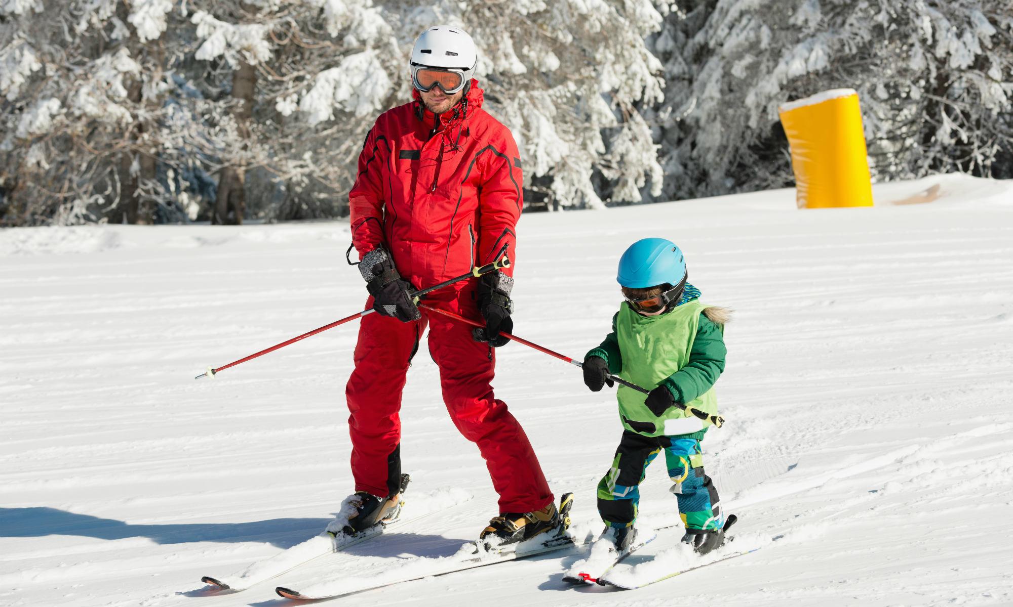 Ein Skilehrer übt das Skifahren mit einem Kind im Rahmen eines privaten Skikurses.