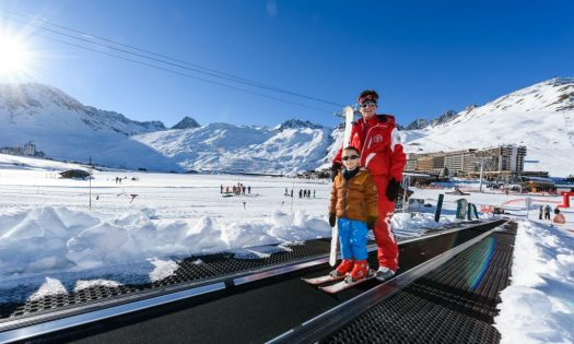 A little child is using the magic carpet to get back up the training area in Tignes.