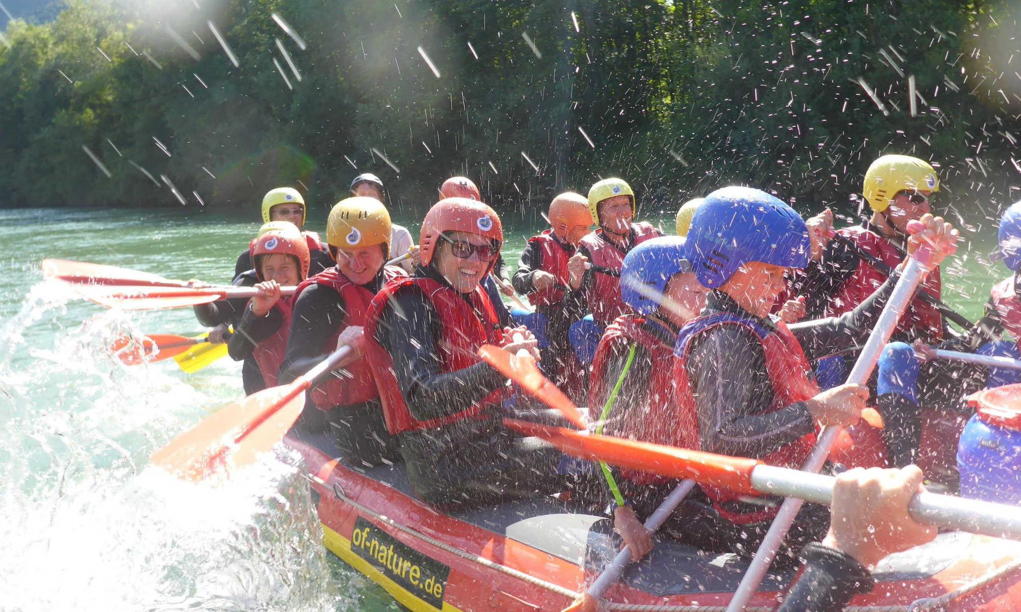 Eine große Gruppe wird bei einer Rafting Tour auf der Iller nassgespritzt.