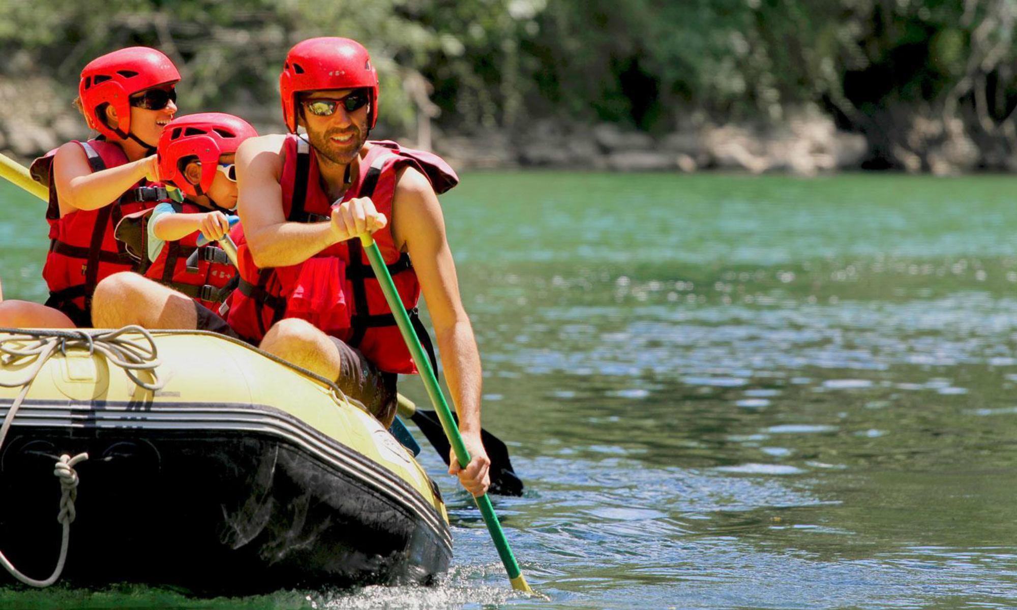 Une famille fait du rafting dans les Pyrénées sur une rivière calme.