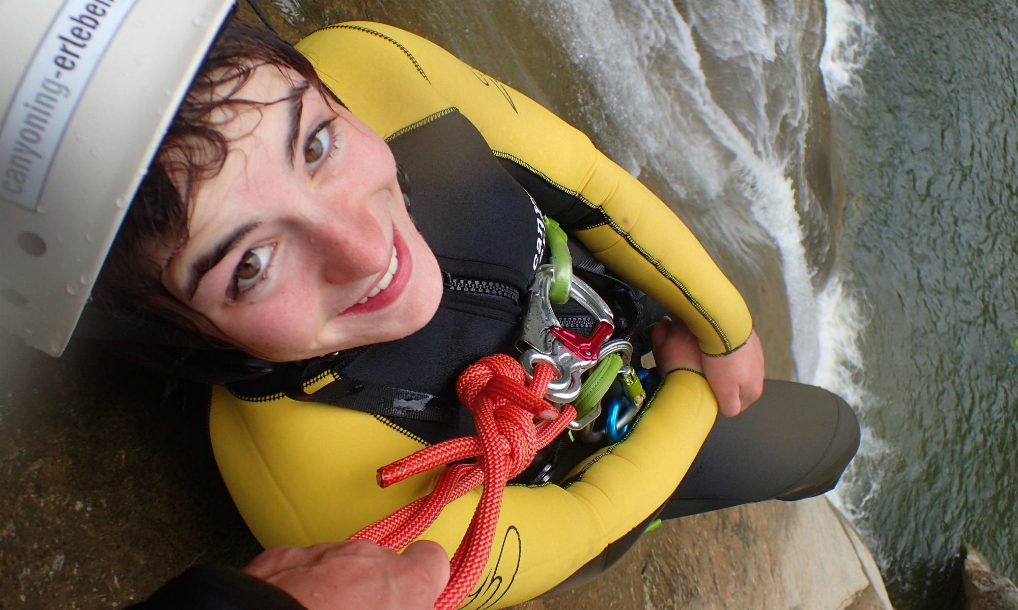 Eine junge Frau hängt beim Canyoning im Allgäu in einer Felswand über einem Wasserbecken und wird nur noch von einer Hand gehalten.