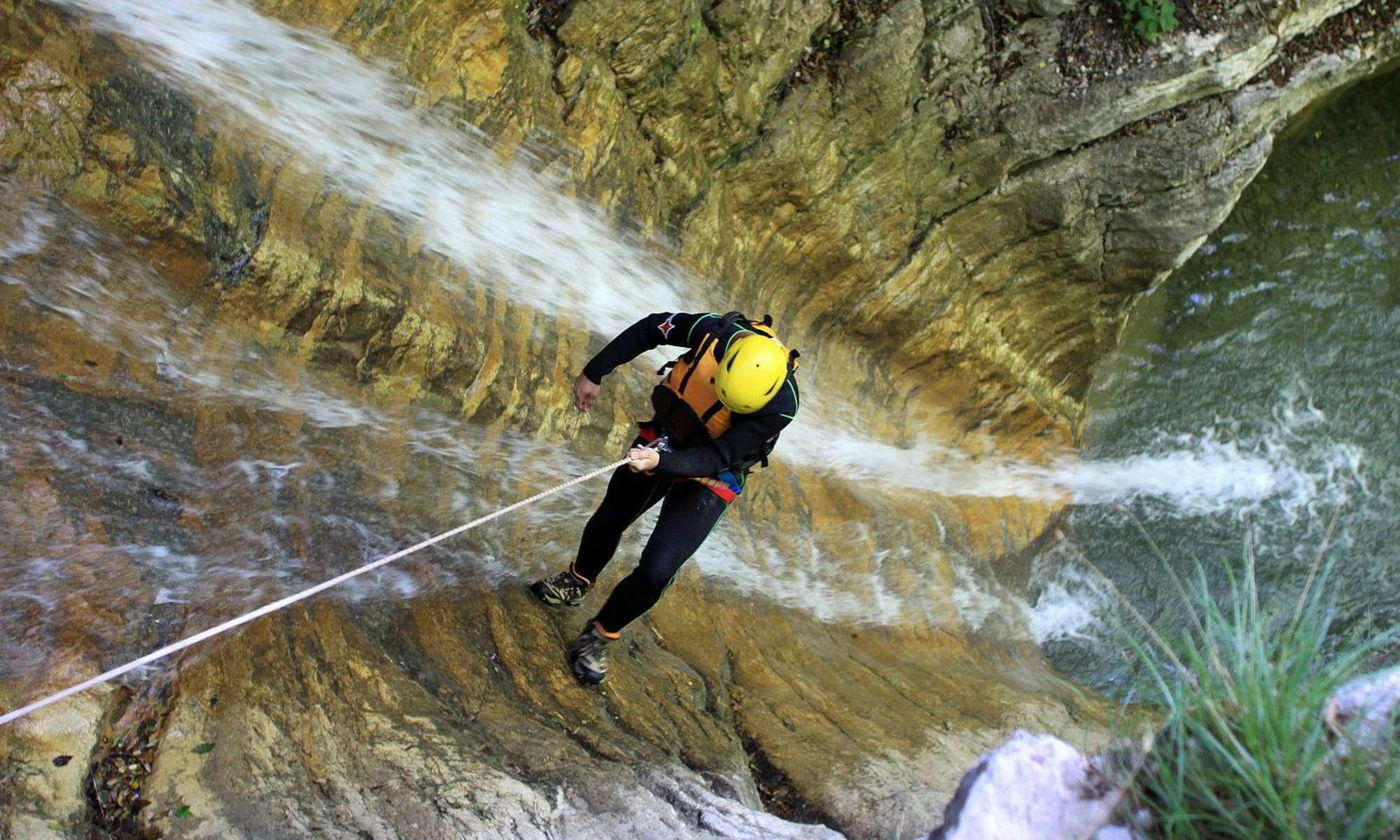 Ein Canyoning Teilnehmer seilt sich einen Wasserfall in der Nähe des Sylvensteinsees ab.