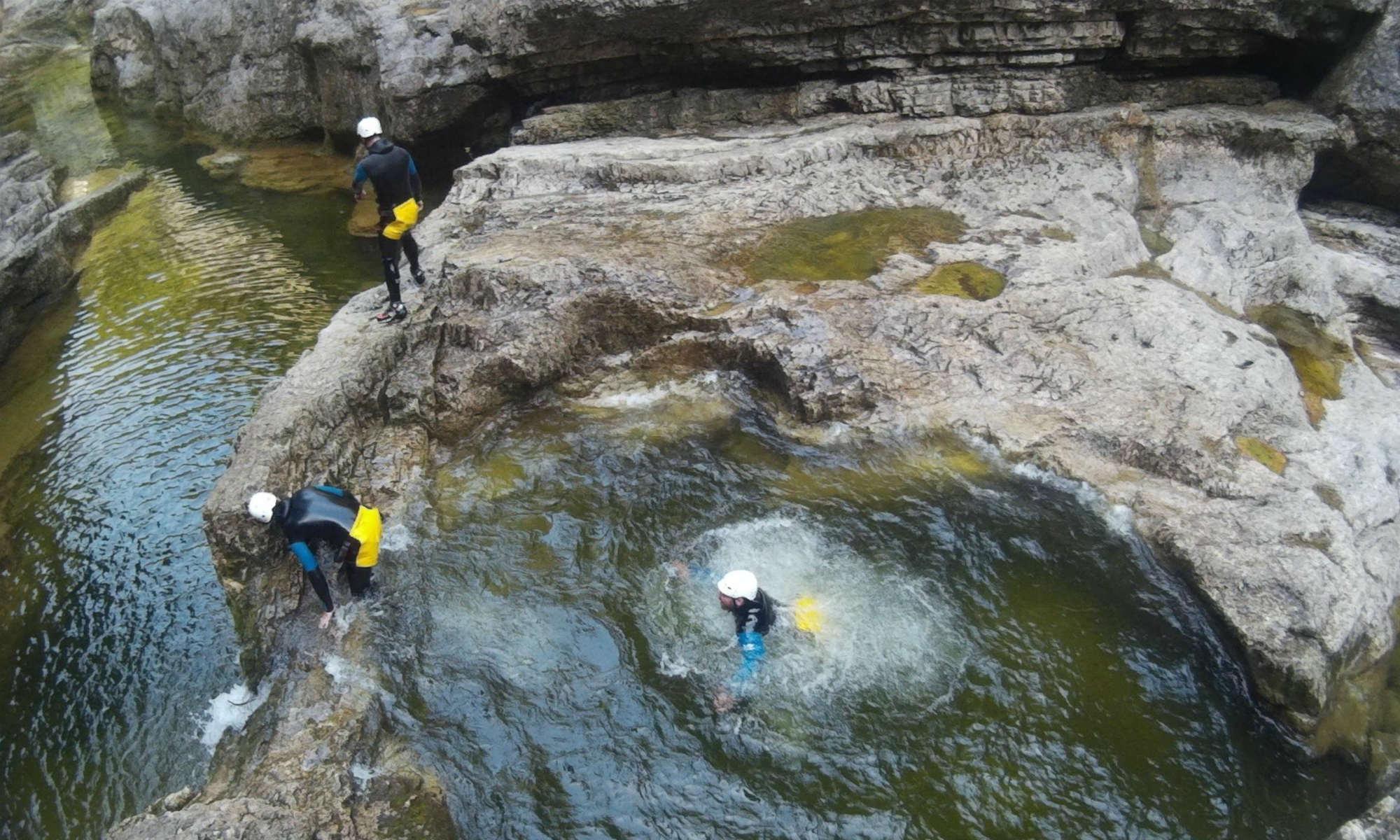 3 Teilnehmer einer Canyoning Tour in der Almbachklamm schwimmen durch natürliche Pools und springen von Felsen in den Fluss.