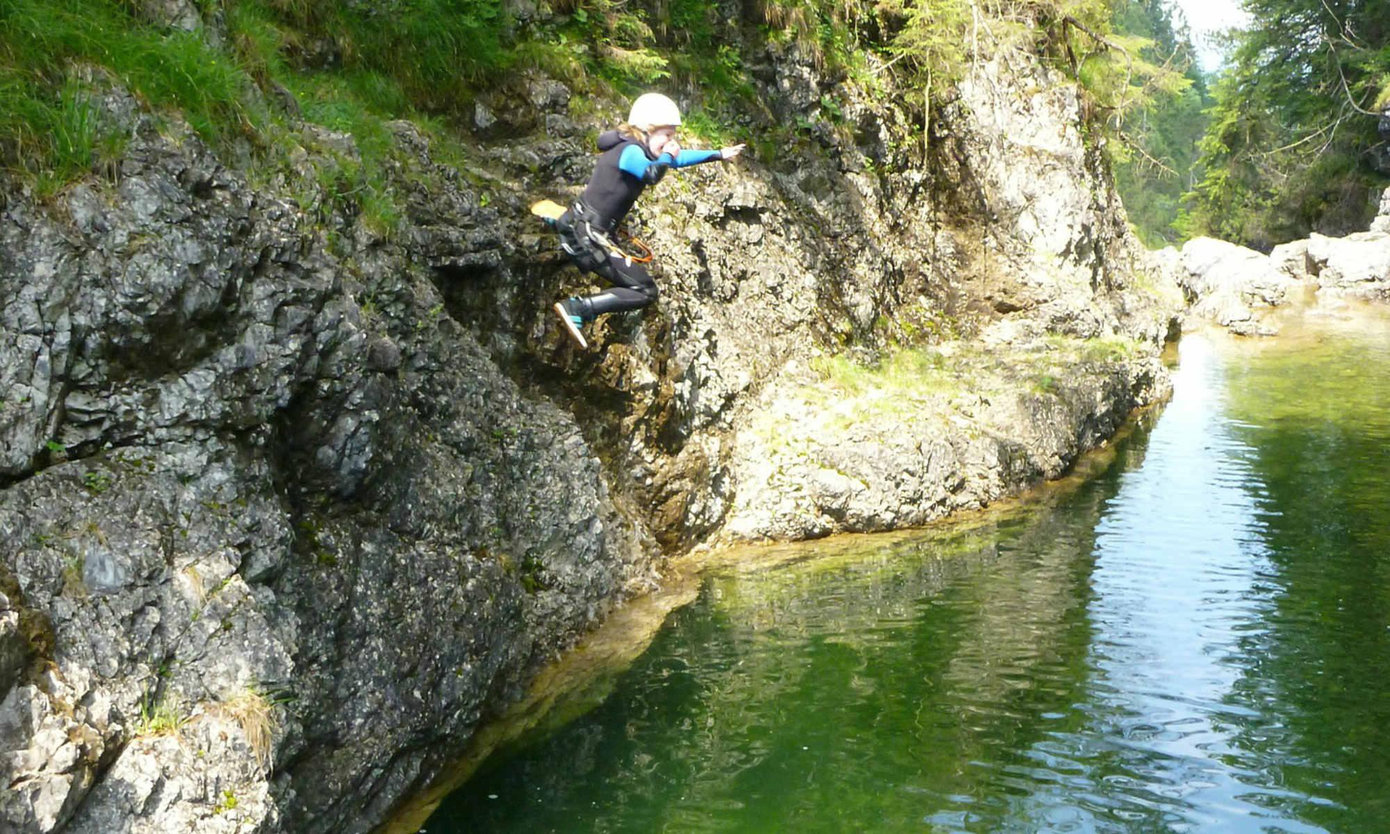Ein Mädchen springt beim Canyoning in der Nähe von Garmisch in smaragdgrünes Wasser.