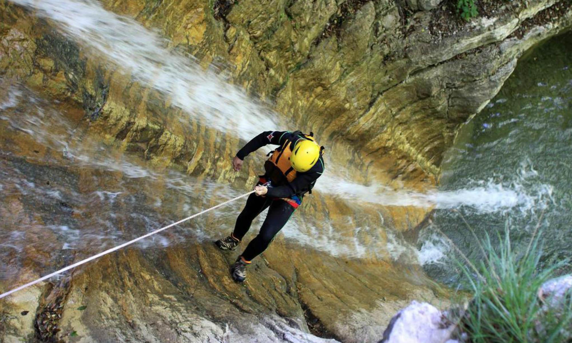 Ein Mann seilt sich beim Canyoning in Deutschland an einem Wasserfall ab.