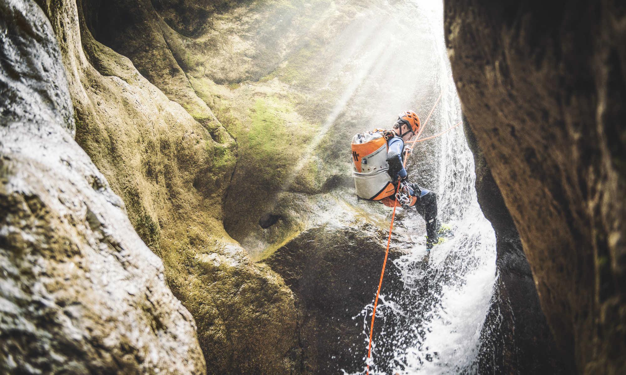 Abseilen bei einem Wasserfall während einer Canyoning Tour im Gesäuse.