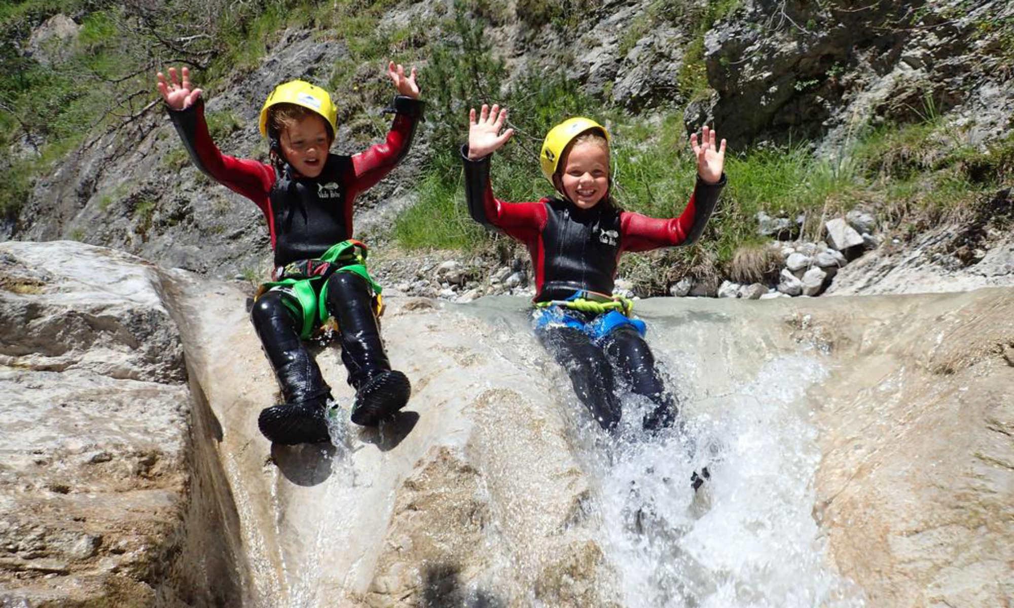 2 Kinder haben auf einer Wasserrutsche beim Canyoning im Oberinntal so richtig Spaß.