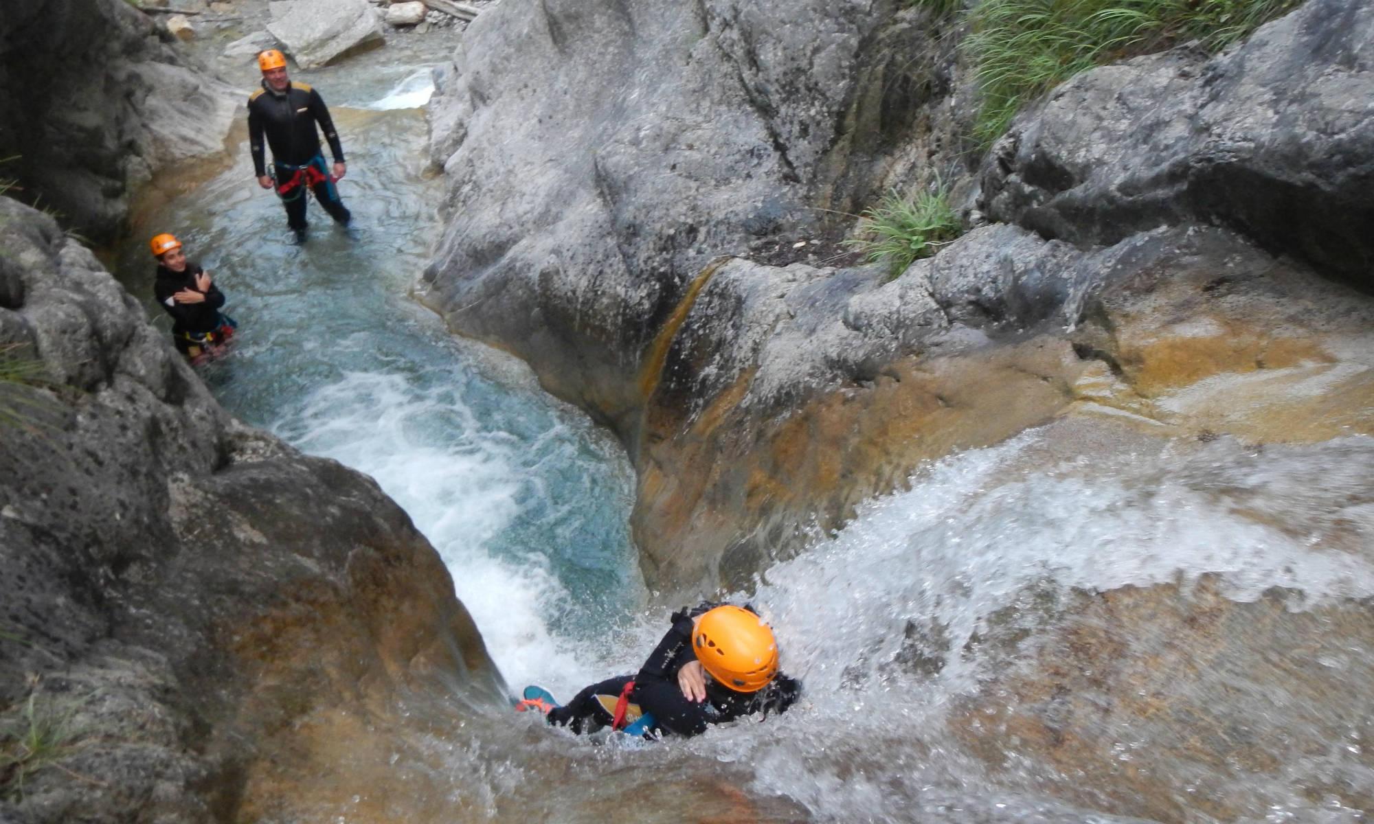 Eine geführte Gruppe rutscht beim Canyoning in Österreich an einer Felswand hinunter.