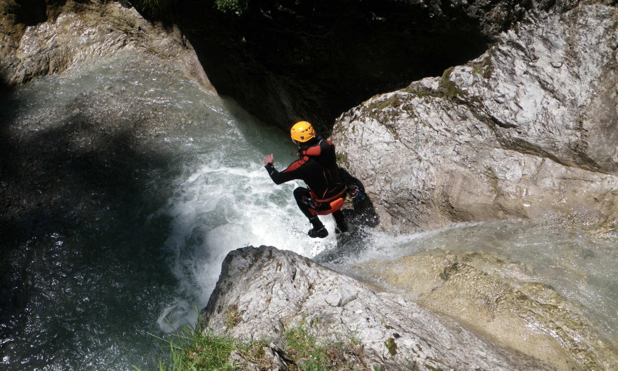 Ein Mann auf einer wasserreichen Felsrutsche beim Canyoning in der Gießenbachklamm in Kiefersfelden.