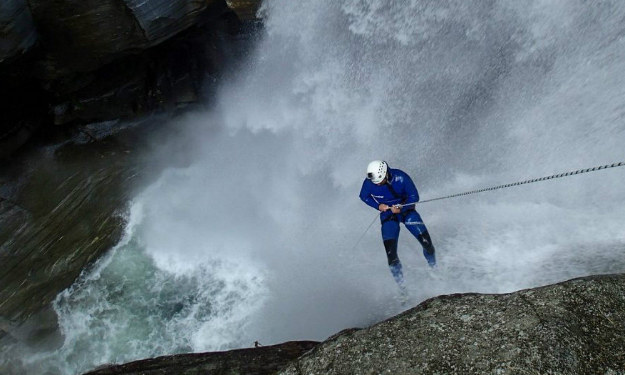Ein Canyoning Teilnehmer seilt sich an einem Wasserfall in der Iragna Schlucht ab