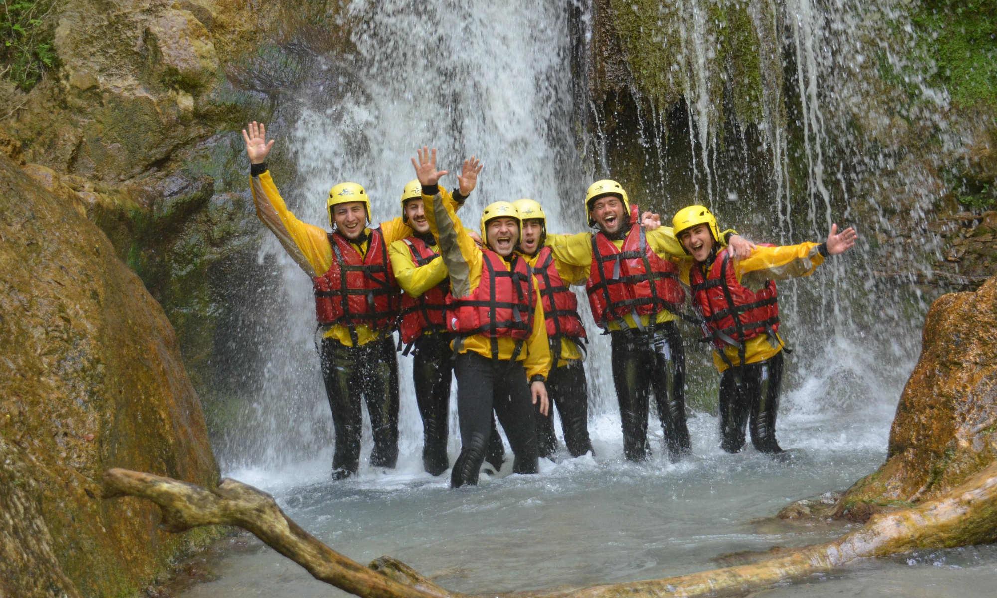 Un gruppo di ragazzi divertiti è in posa sotto una cascata nel fiume Lao.