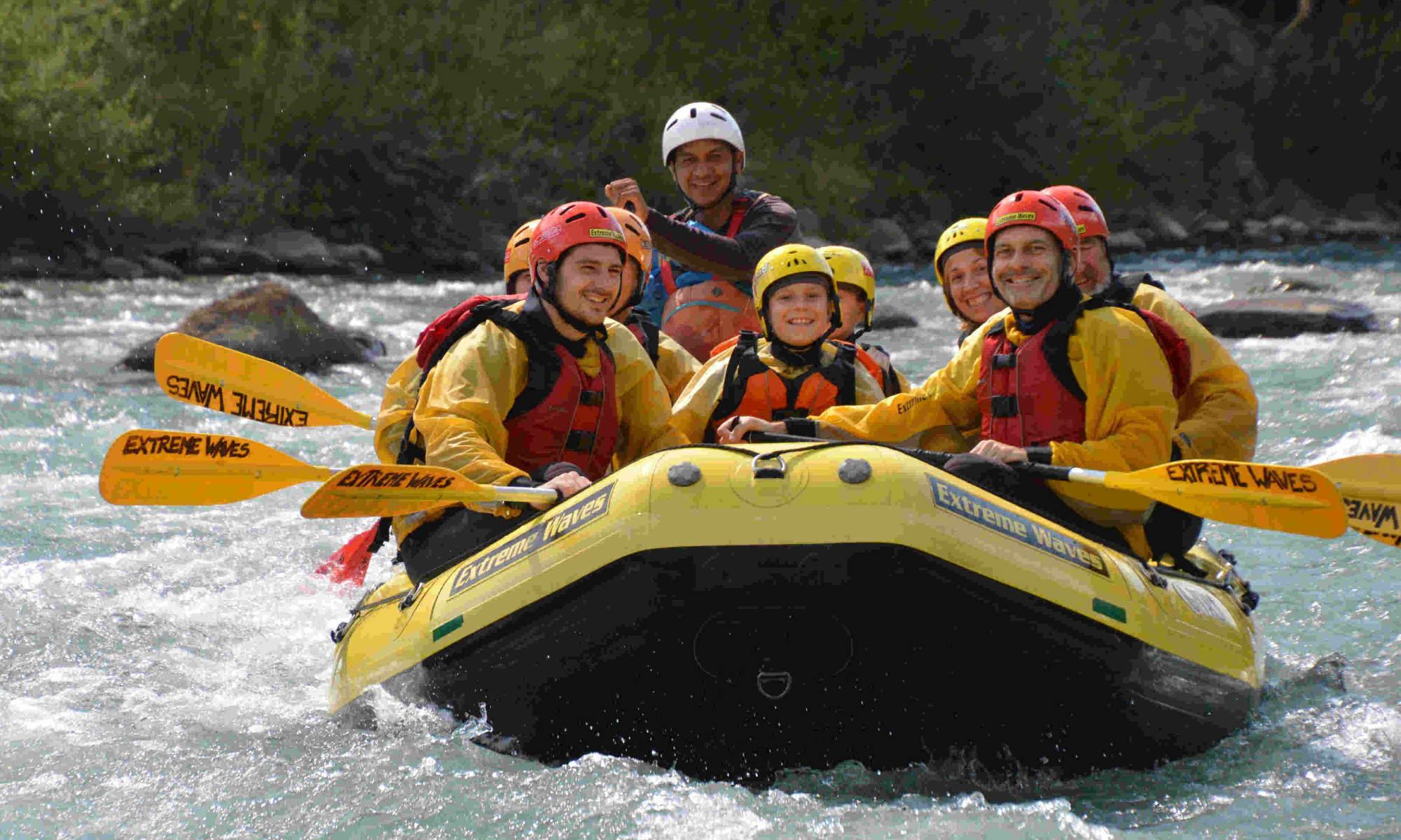 Un gruppo sorridente di persone, tra cui compaiono anche dei bambini, fa rafting sul fiume Noce in Val di Sole.