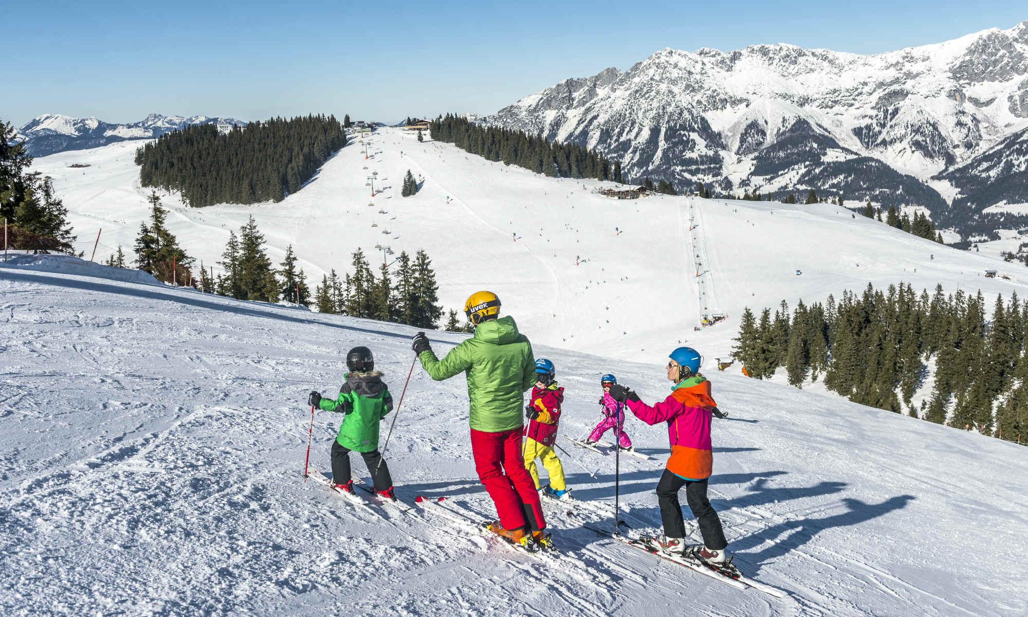 Eine Familie beim Skifahren auf der Piste mit Bergpanorama.