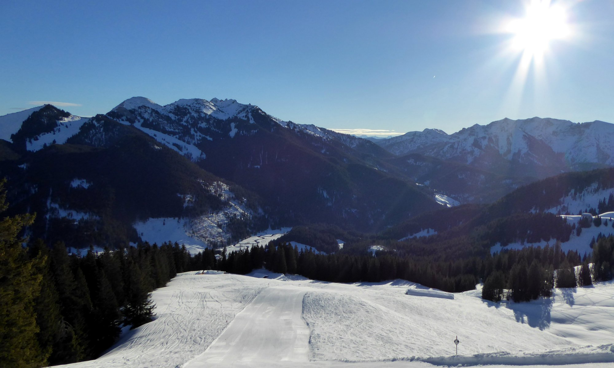 Blick auf sonnige Skipisten im Skigebiet Tegernsee.