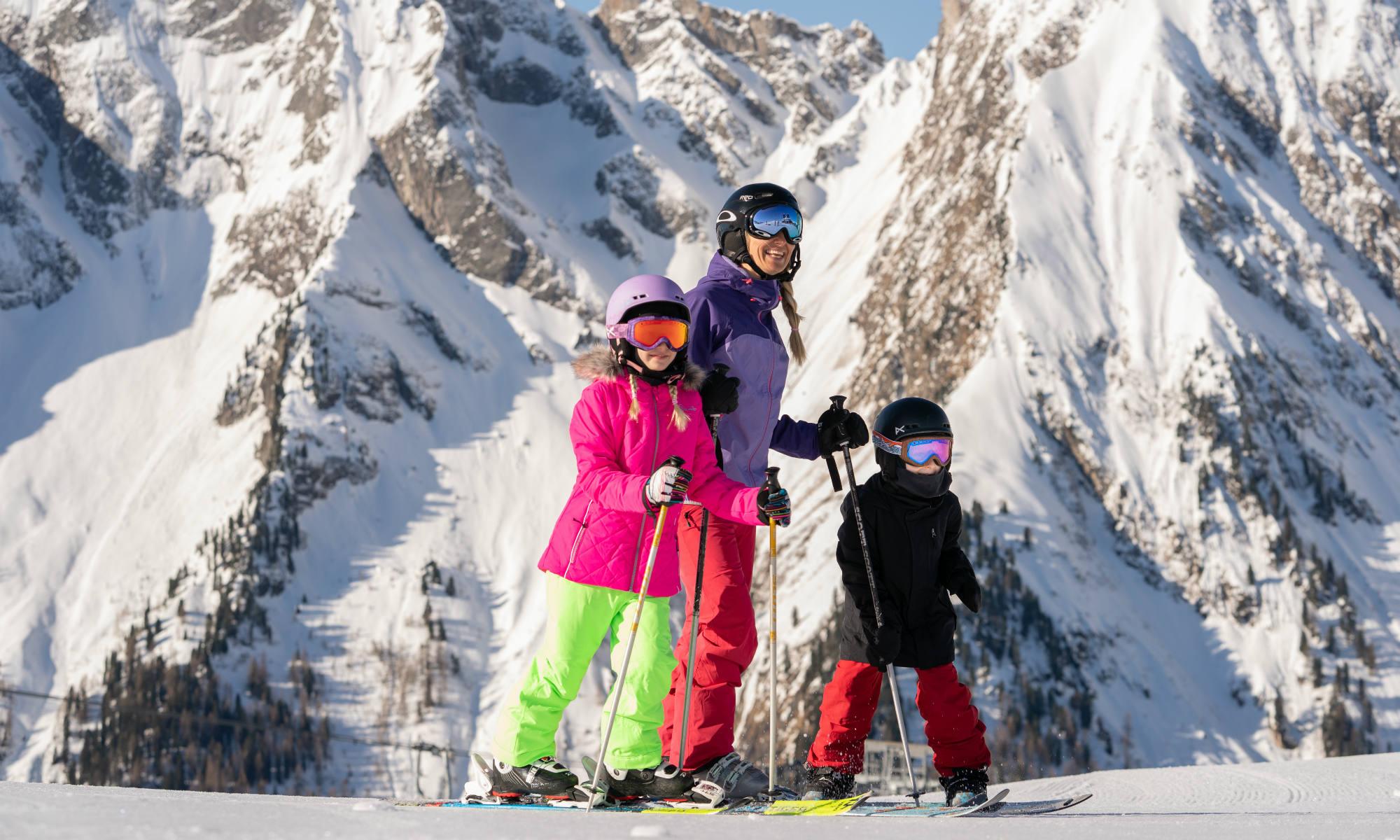 Mutter mit 2 Kindern auf Skiern vor dem Bergpanorama des Zillertals.
