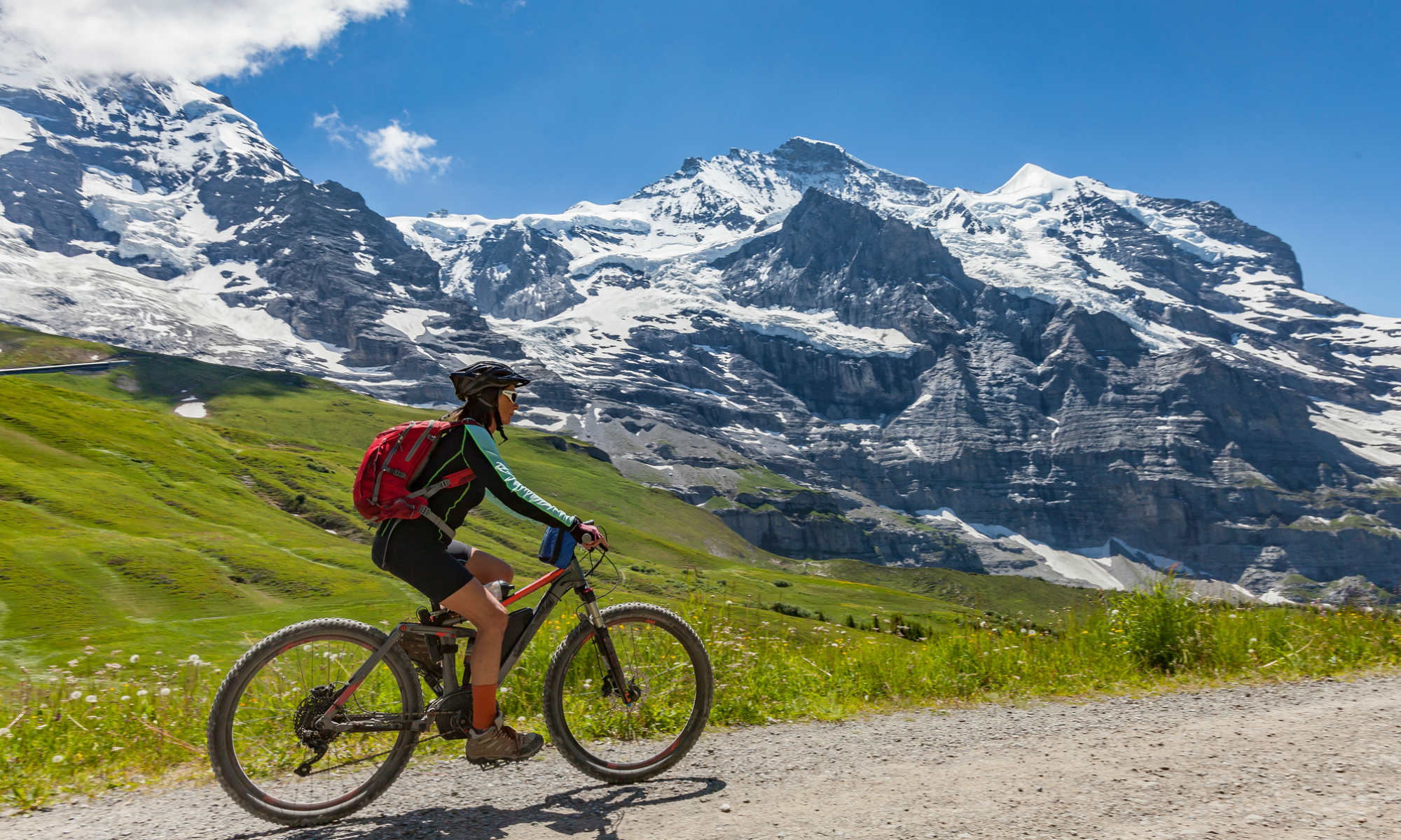 A cyclist is enjoying a sunny day in the mountains.