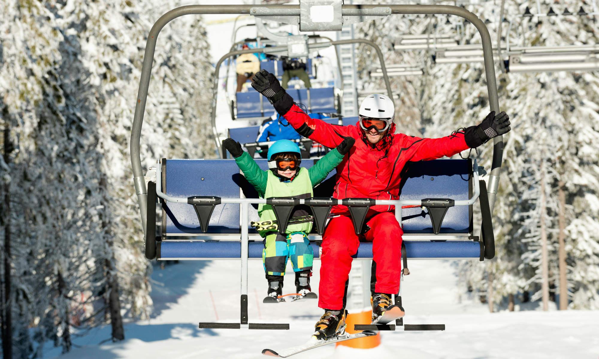 Un jeune skieur et son moniteur de ski sur un télésiège.