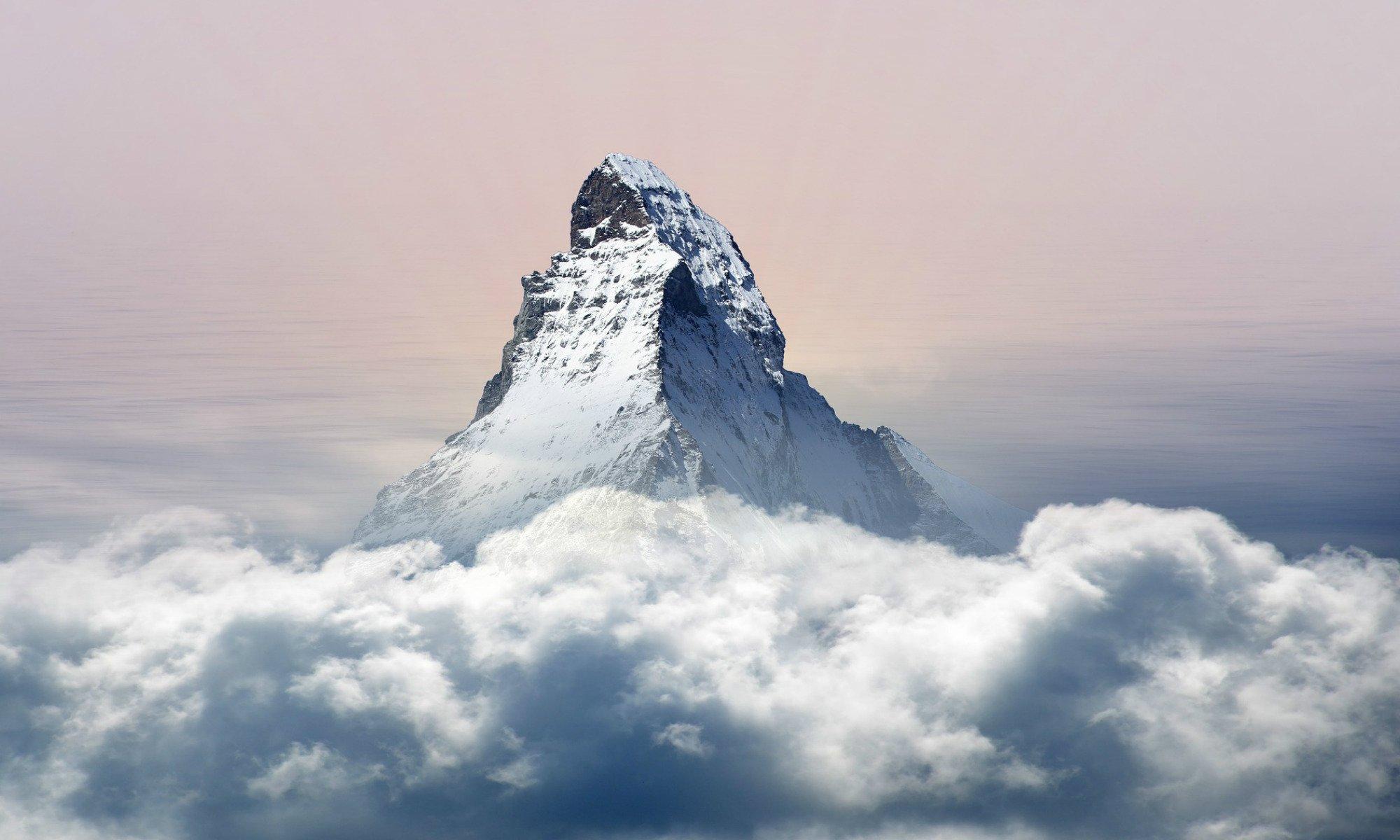 Une haute montagne se dresse dans le ciel au dessus des nuages.