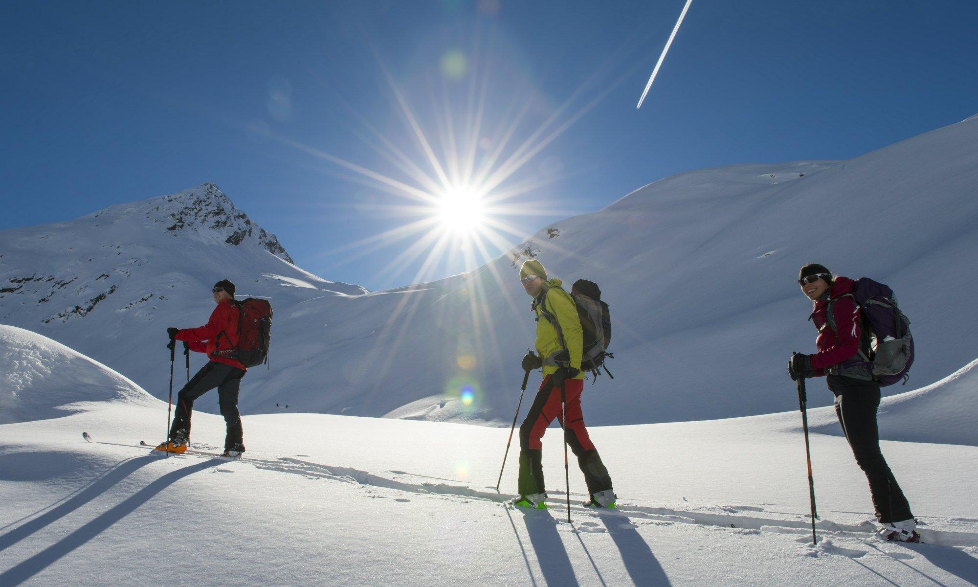 3 persone in un tour sciistico attraverso il paesaggio montano innevato.