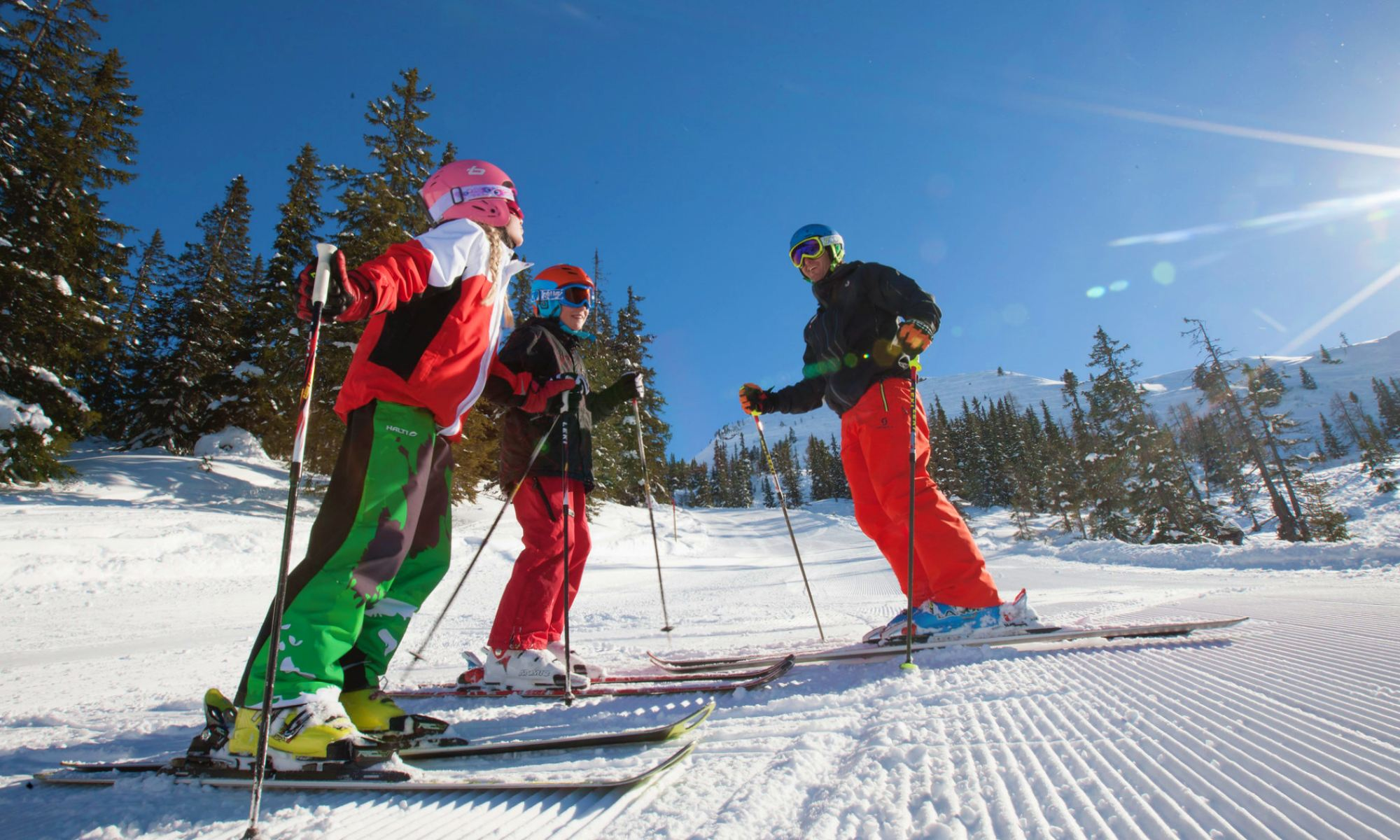 An instructor plus two skiers on the slopes.