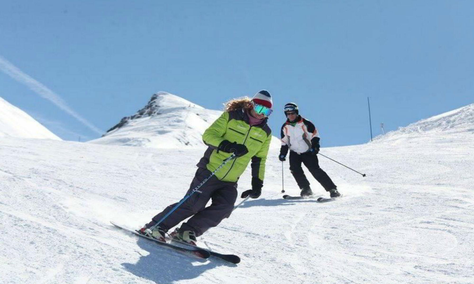 Un moniteur particulier de ski et son élève sur une piste enneigée.