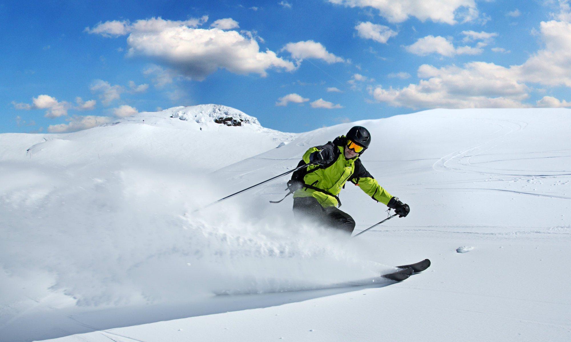 Uno sciatore si diverte nella neve fresca.