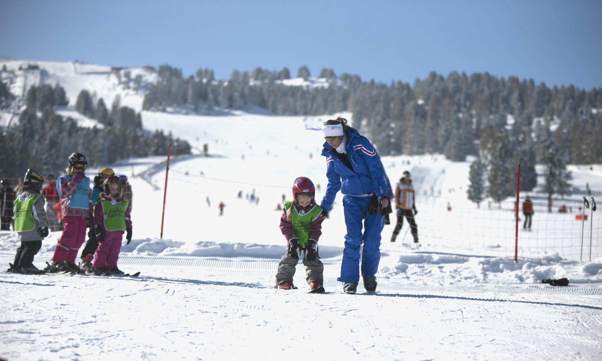 Un bambino piccolo scia in un corso di gruppo con un maestro di sci.