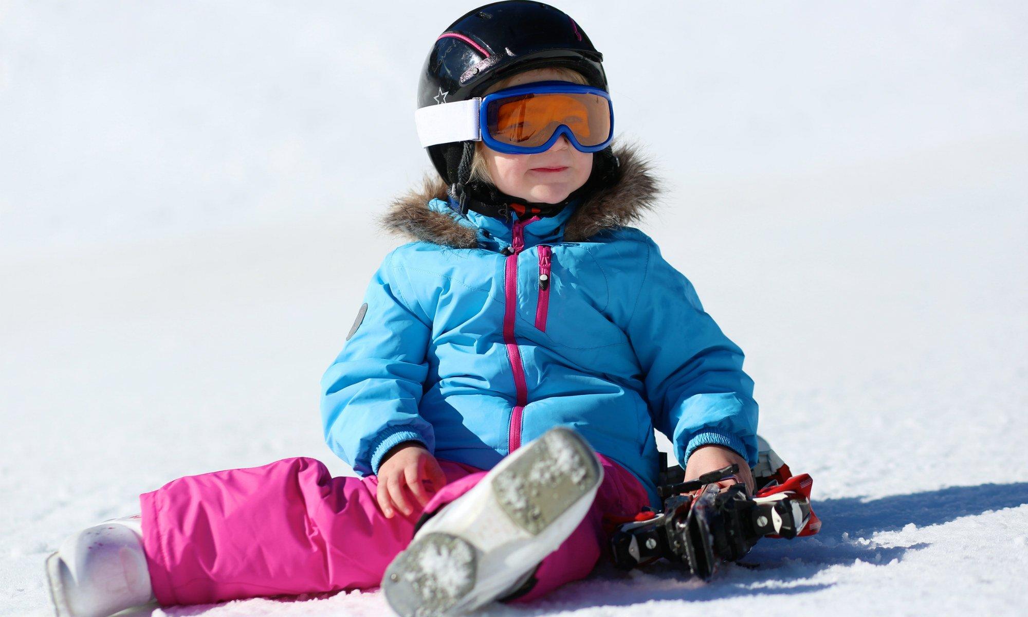Una bambina è seduta sulla neve.