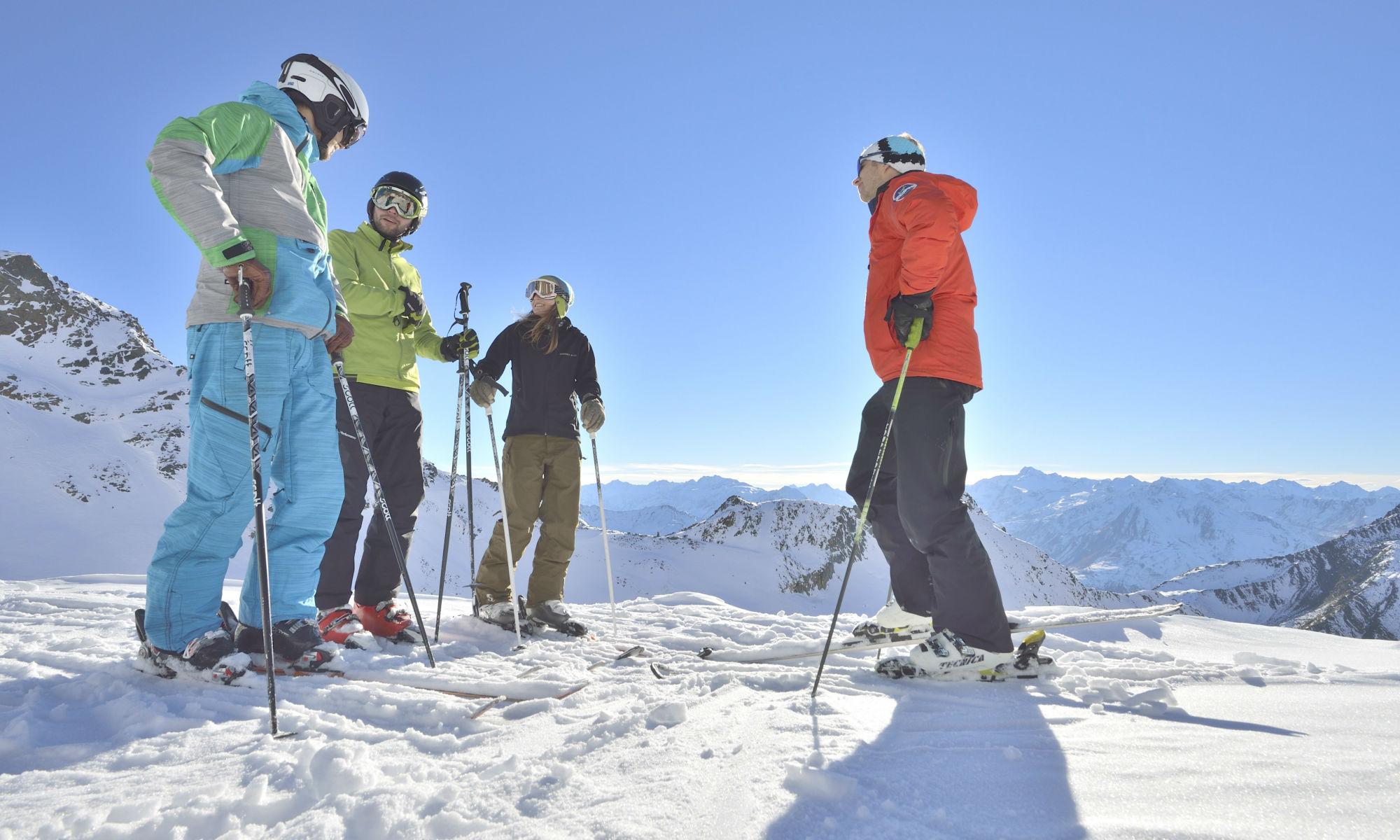 Eine kleine Skikurs Gruppe auf einem Berggipfel.