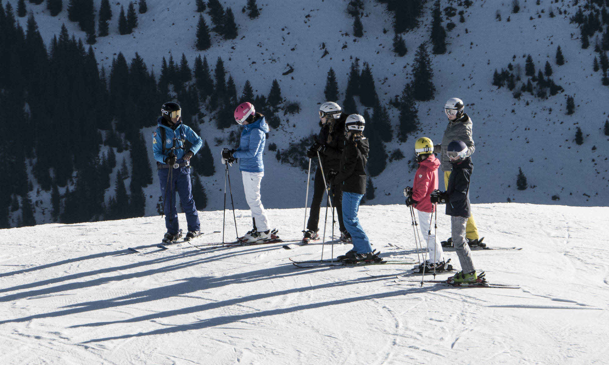 Un gruppo di 6 sciatori ascolta le istruzioni del maestro di sci.