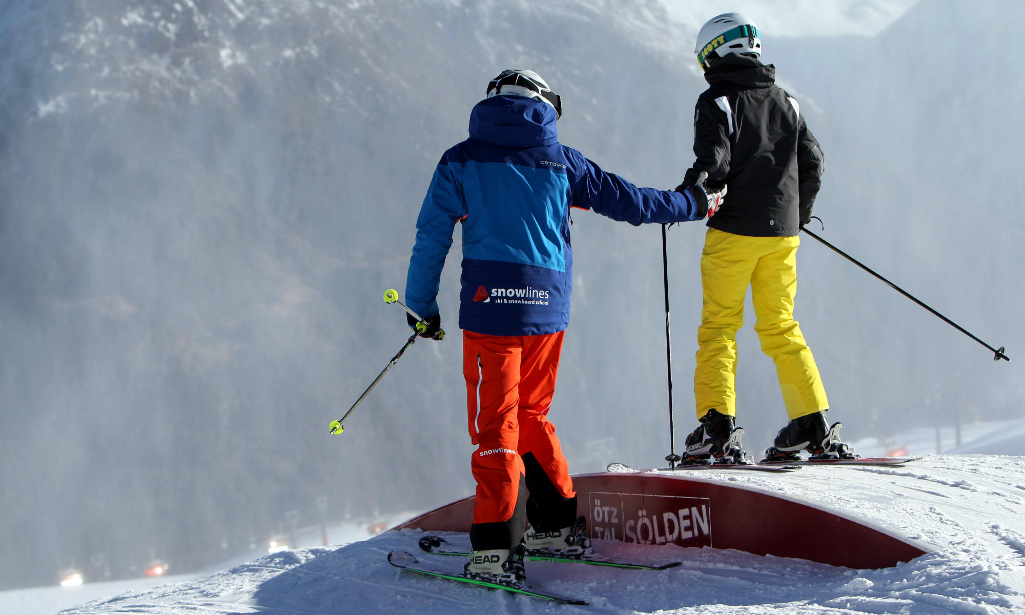 A child and a ski instructor practising freestyle techniques.