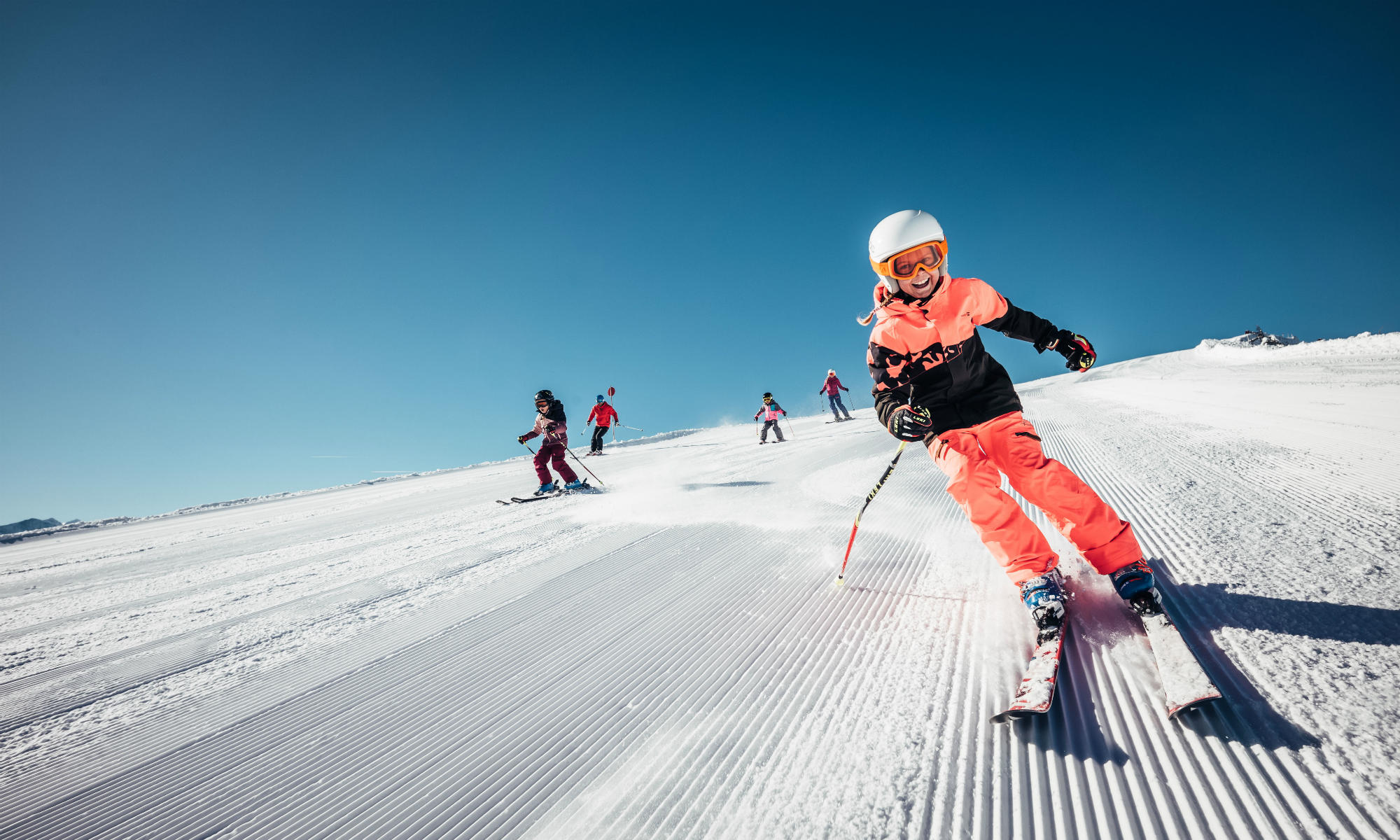 A group of children skiing on a perfectly groomed piste in the Austrian ski resort Zell am See-Kaprun.