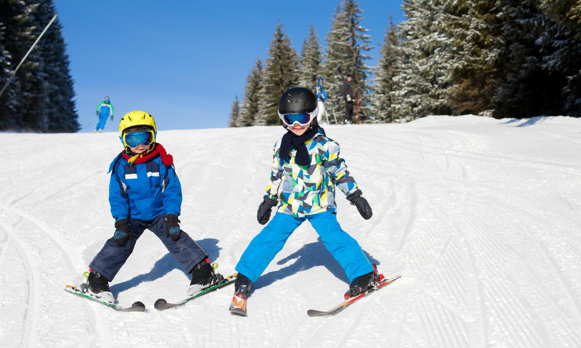 Zwei Kinder üben auf einer blauen Piste den Schneepflug.