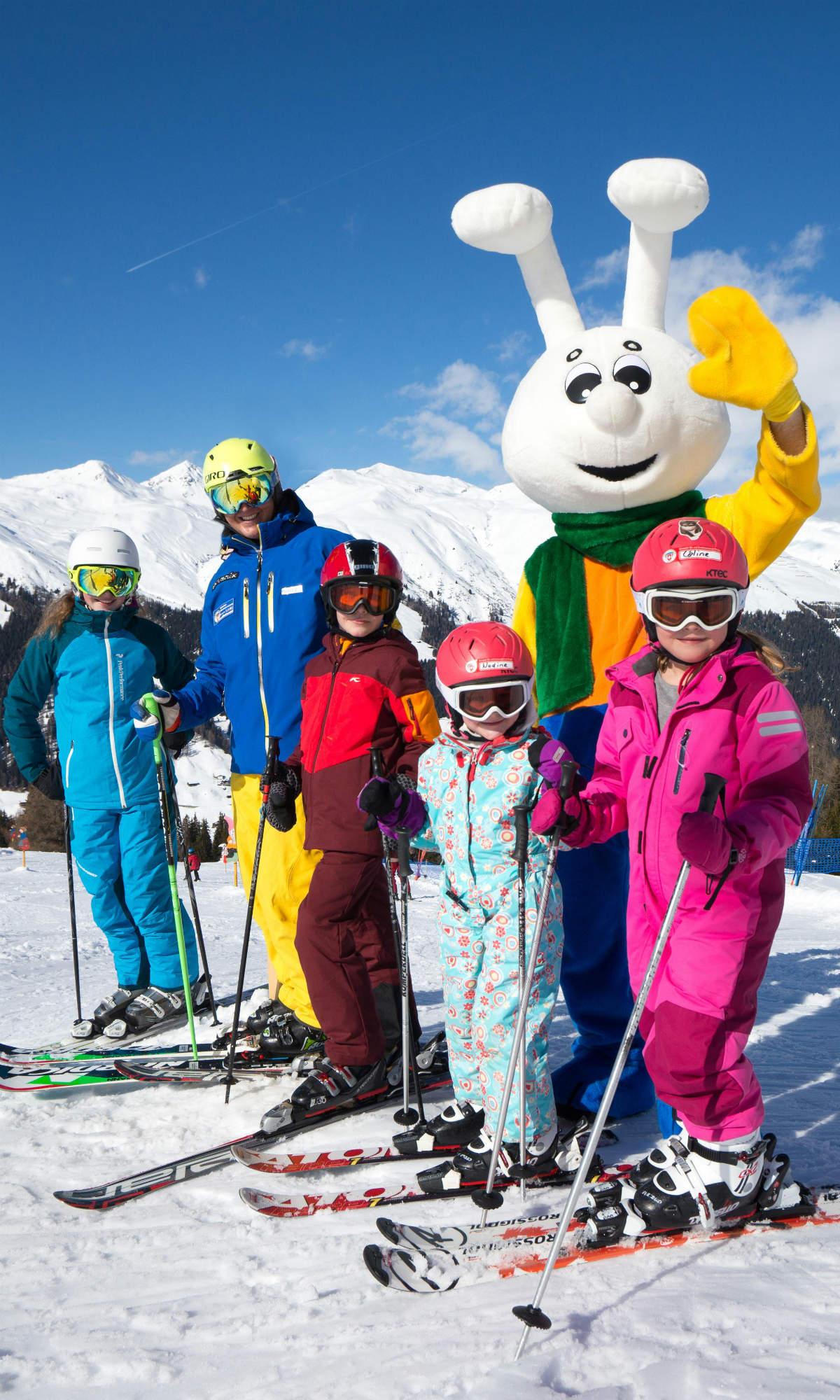 Kinder beim Skikurs gemeinsam mit Maskottchen Snowli in Davos.