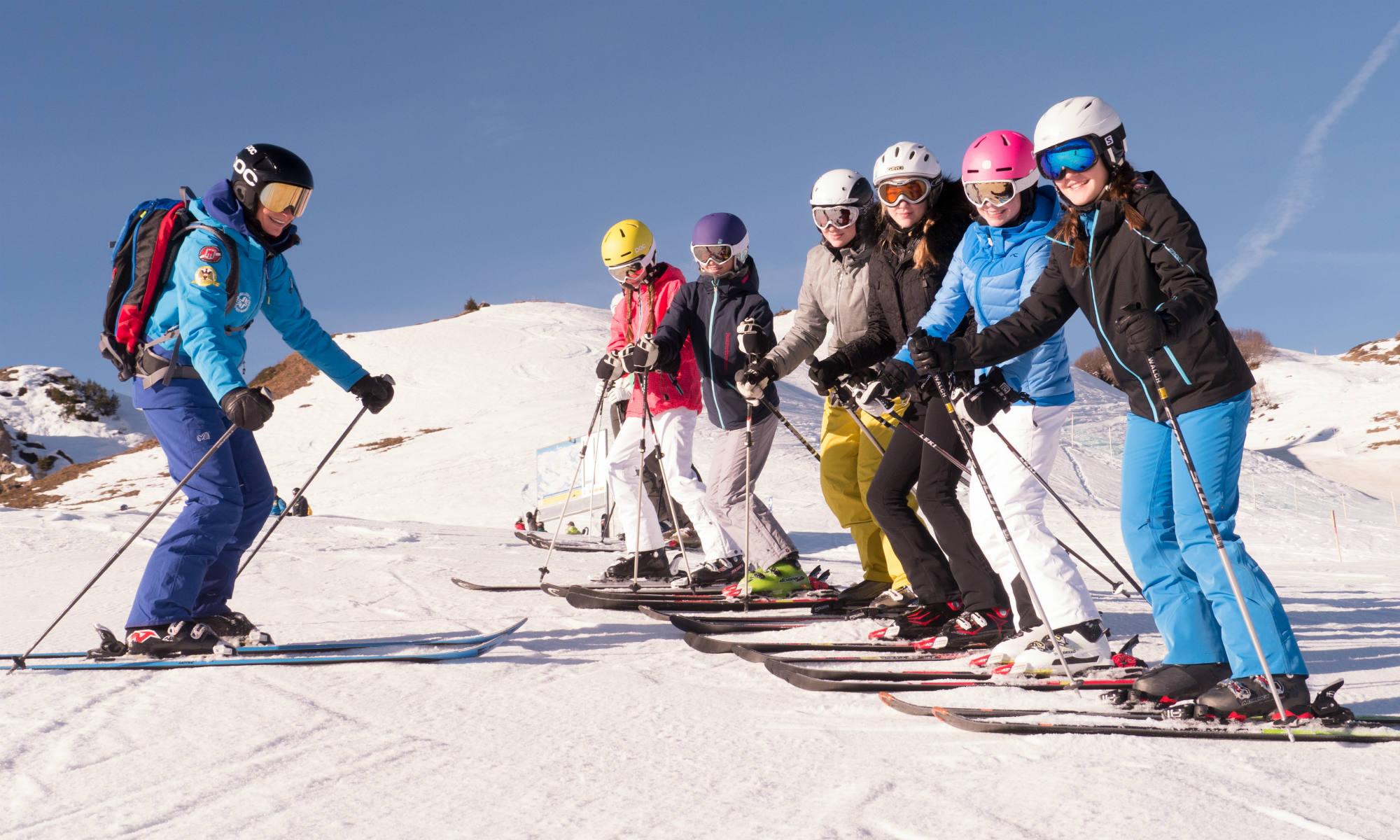 Eine Skilehrerin beim Skikurs mit Teenagern auf Skipiste bei sonnigem Wetter.