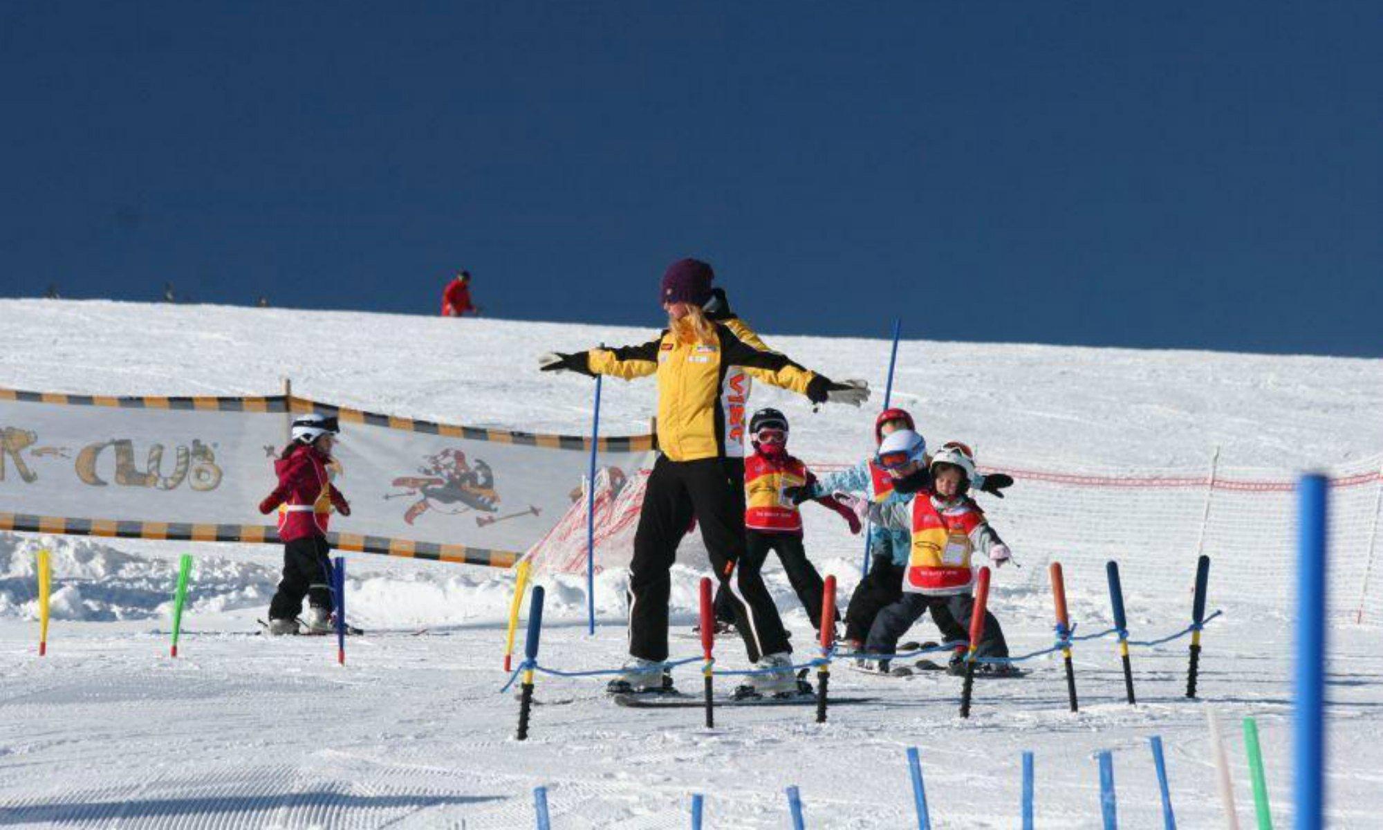 Ein Skilehrer mit einer Gruppe von Kindern beim Üben im Kinderland.