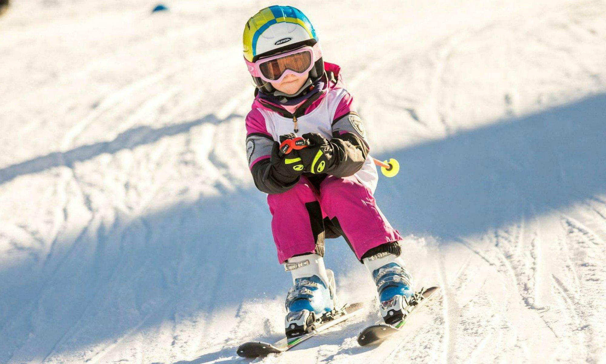 Ein Mädchen beim Skifahren in der Abfahrtshocke.