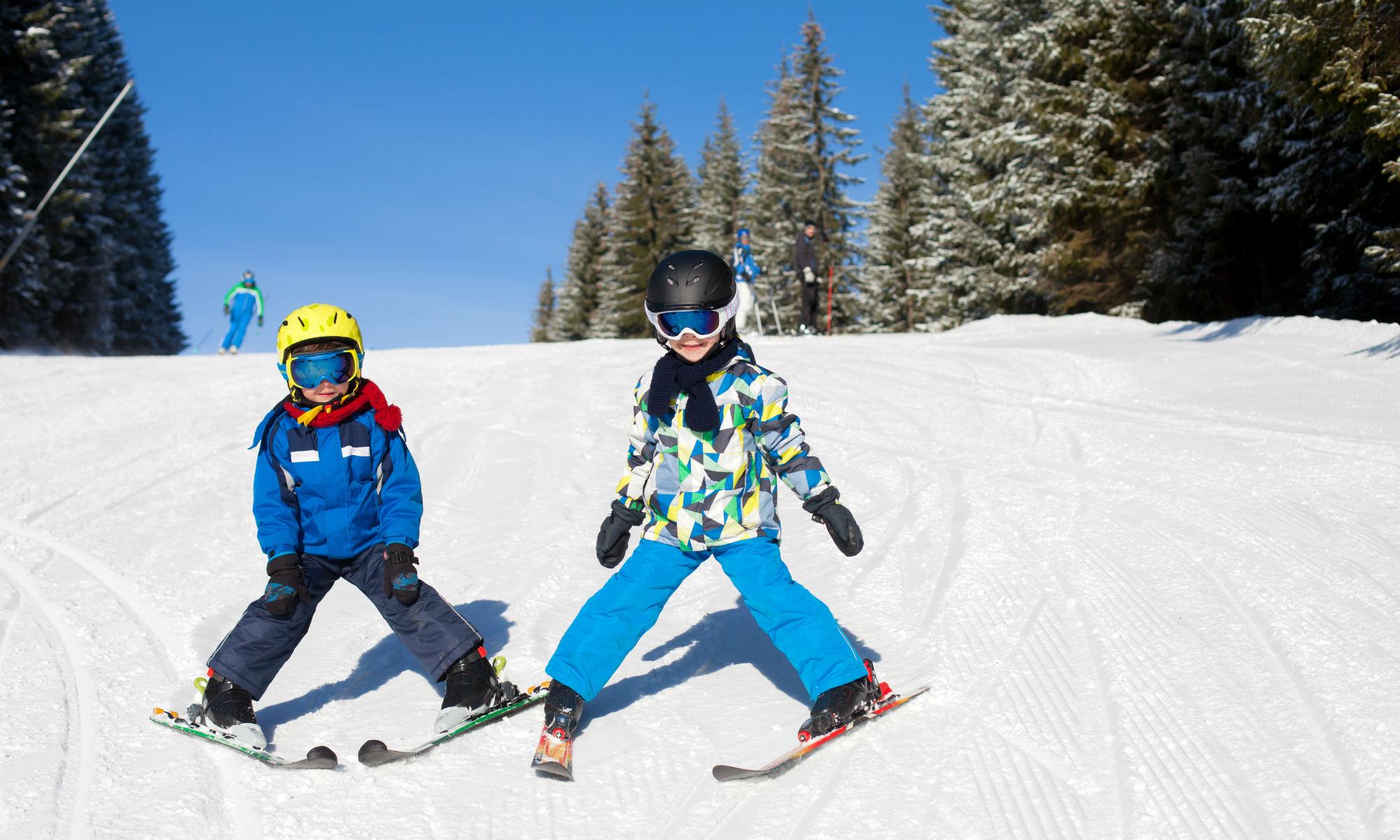 2 Kinder auf Skiern beim Pflug fahren auf der sonnigen Piste.