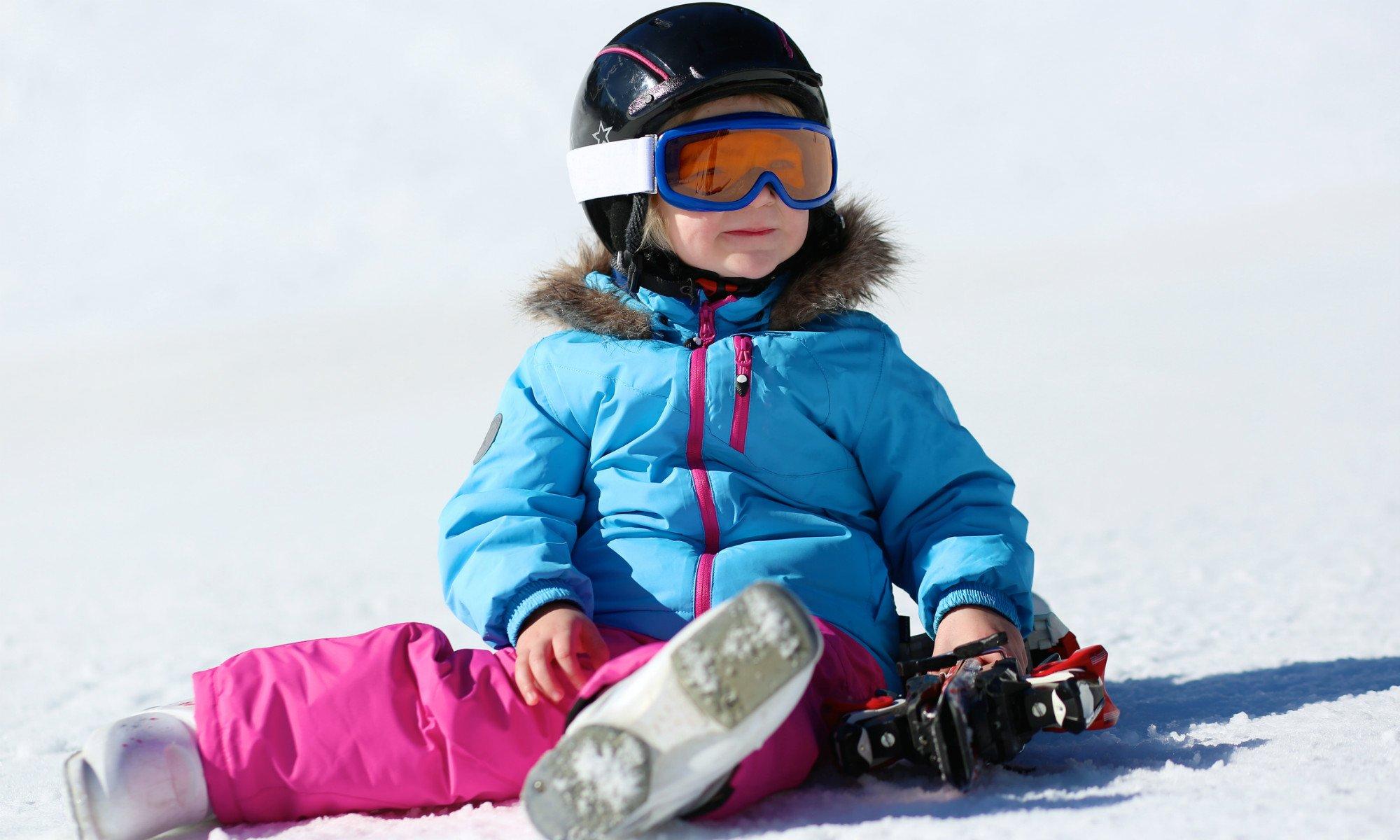 Ein Kleinkind sitzt in Skiausrüstung im Schnee.