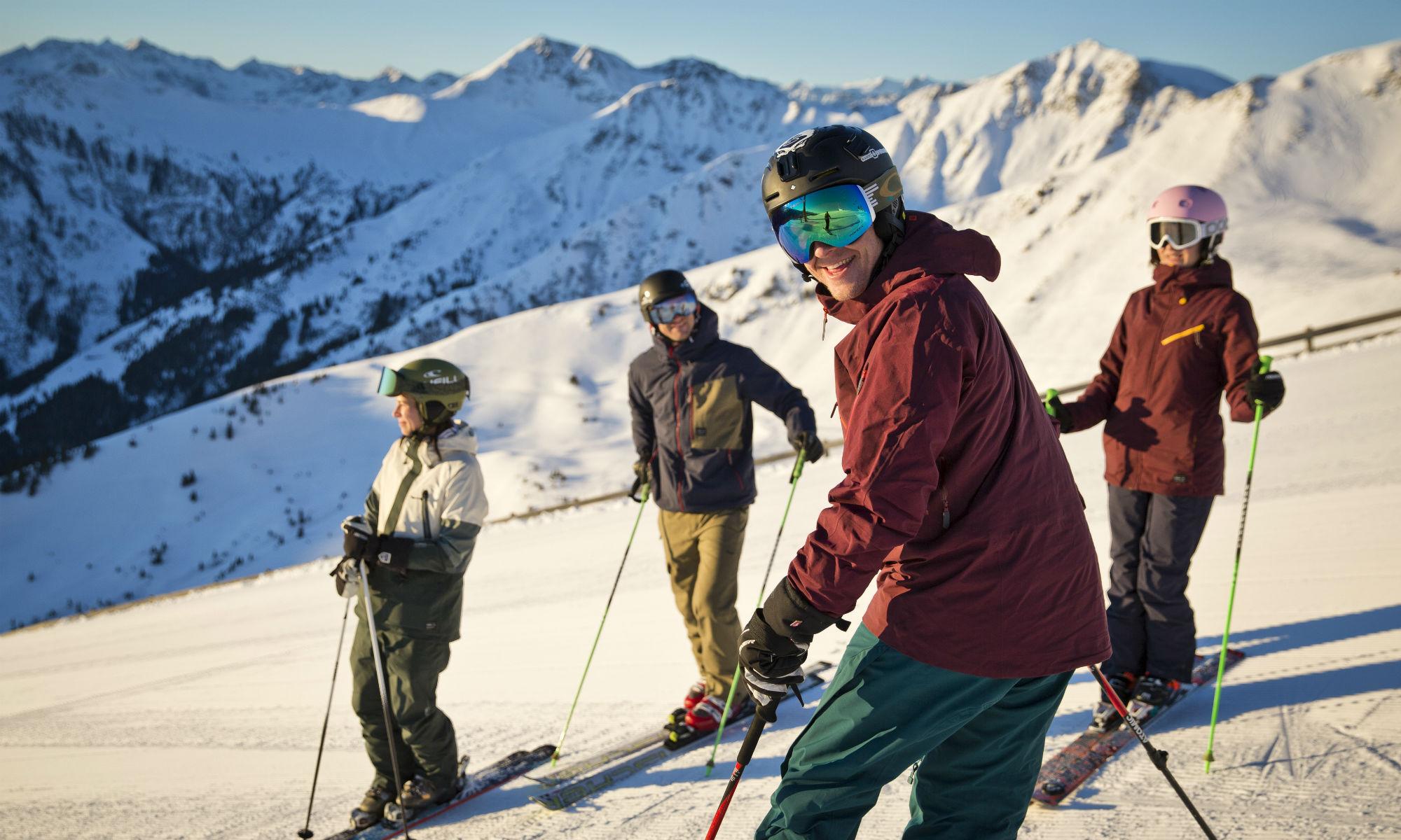 4 Personen mit Skiausrüstung auf der sonnigen Piste in Saalbach-Hinterglemm.