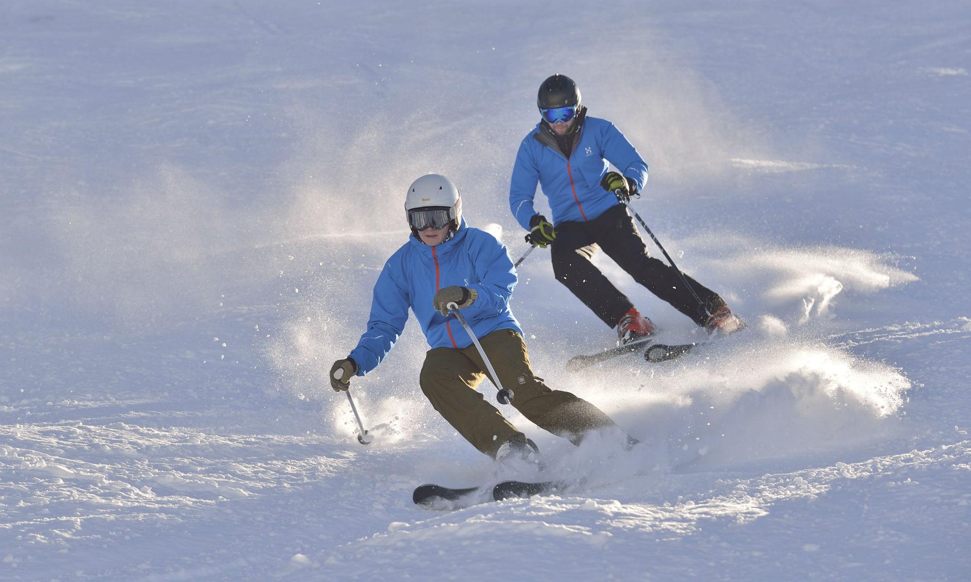2 Skifahrer beim Üben der Skitechnik auf der sonnigen Piste.