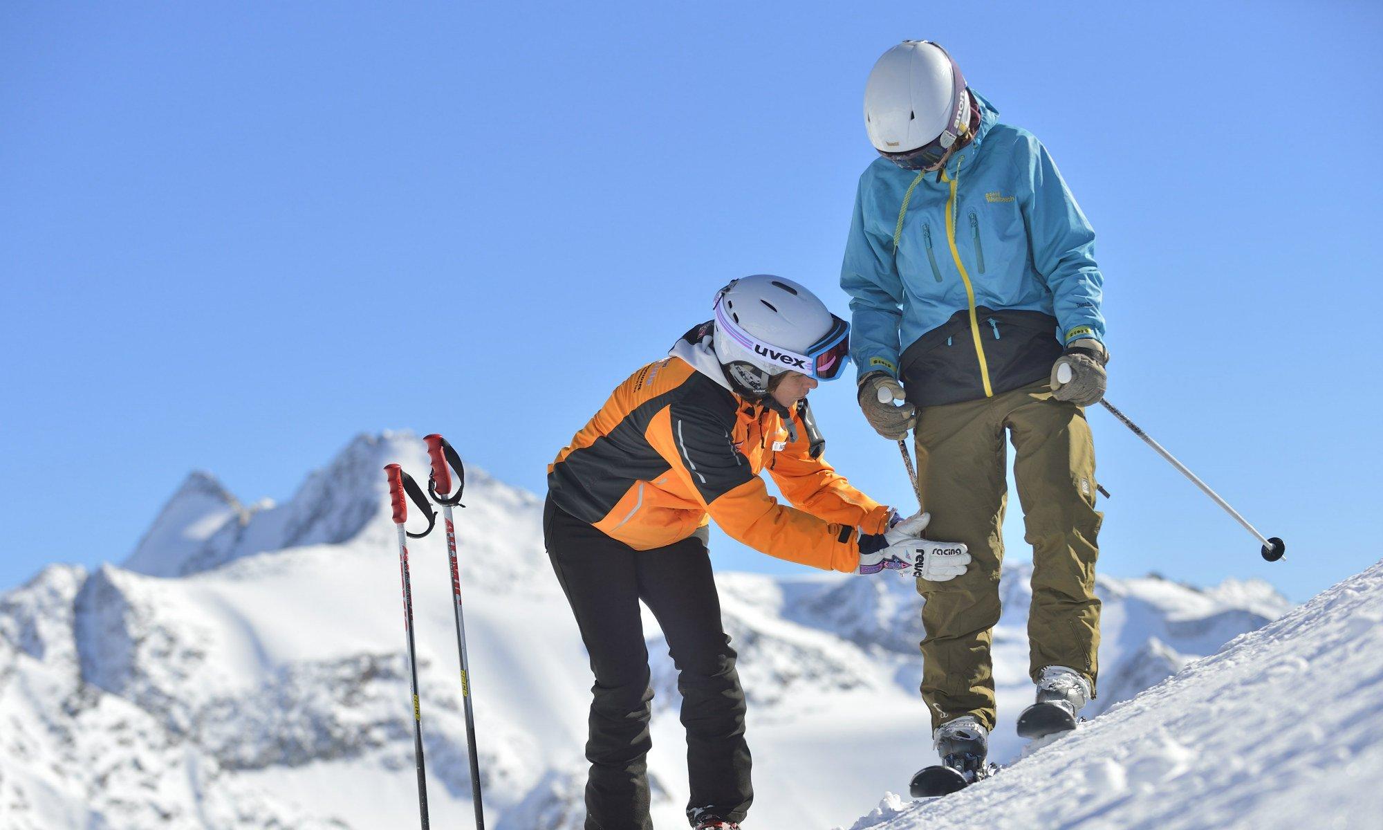 Eine Skilehrerin zeigt einem Anfänger die richtige Technik.