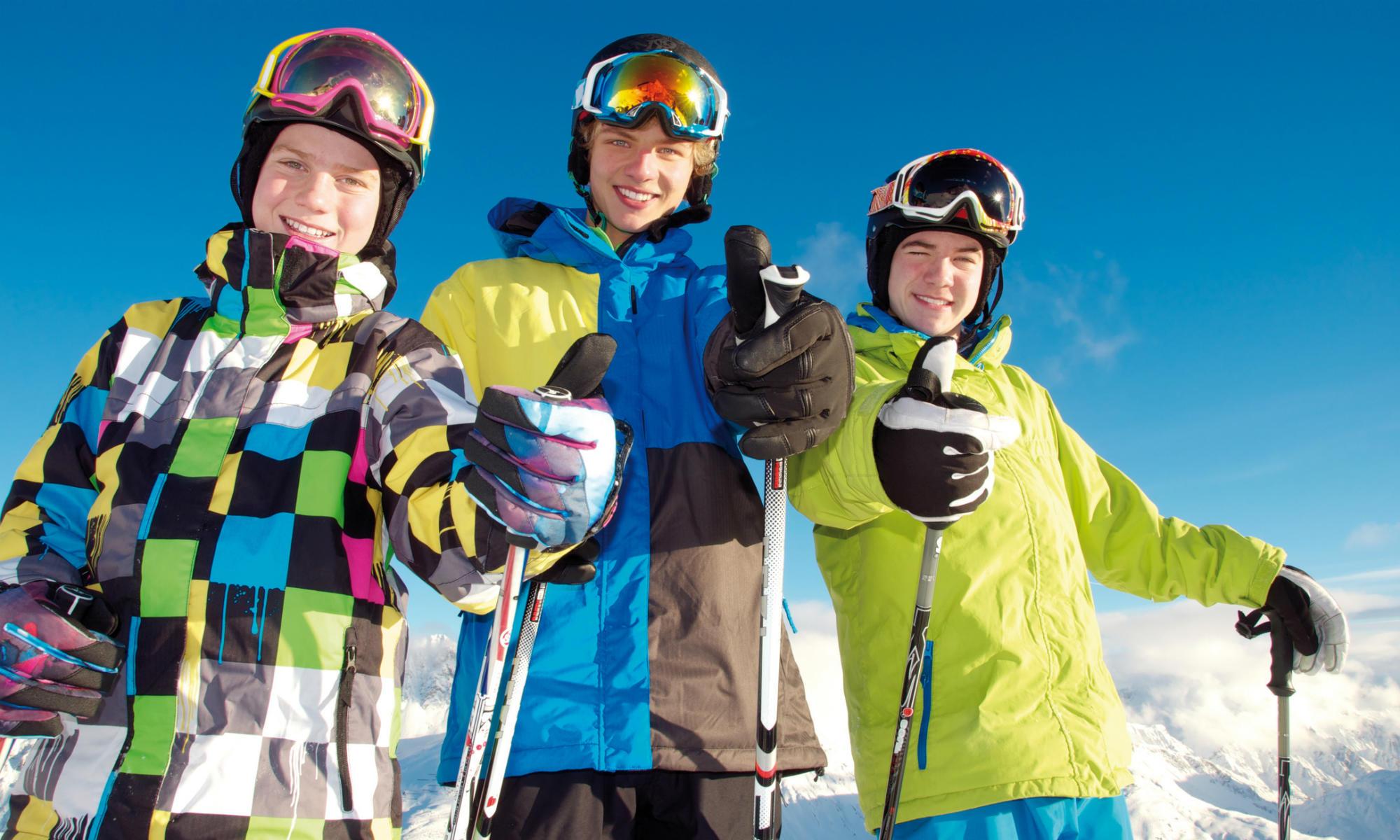3 Teenager beim Skifahren zeigen Daumen hoch.