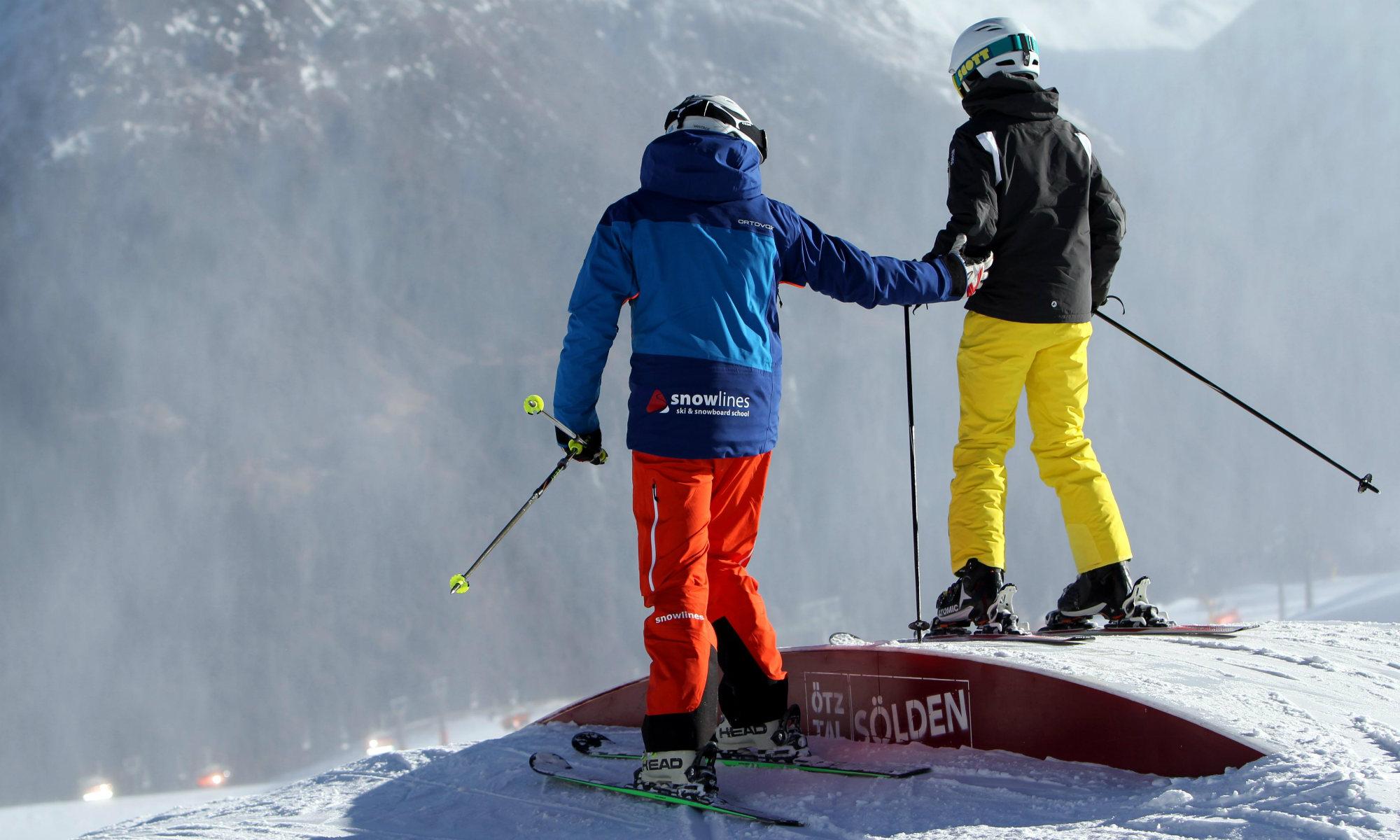 Ein Skilehrer hilft einem Teenager beim Erlernen eines Freestyle Tricks.