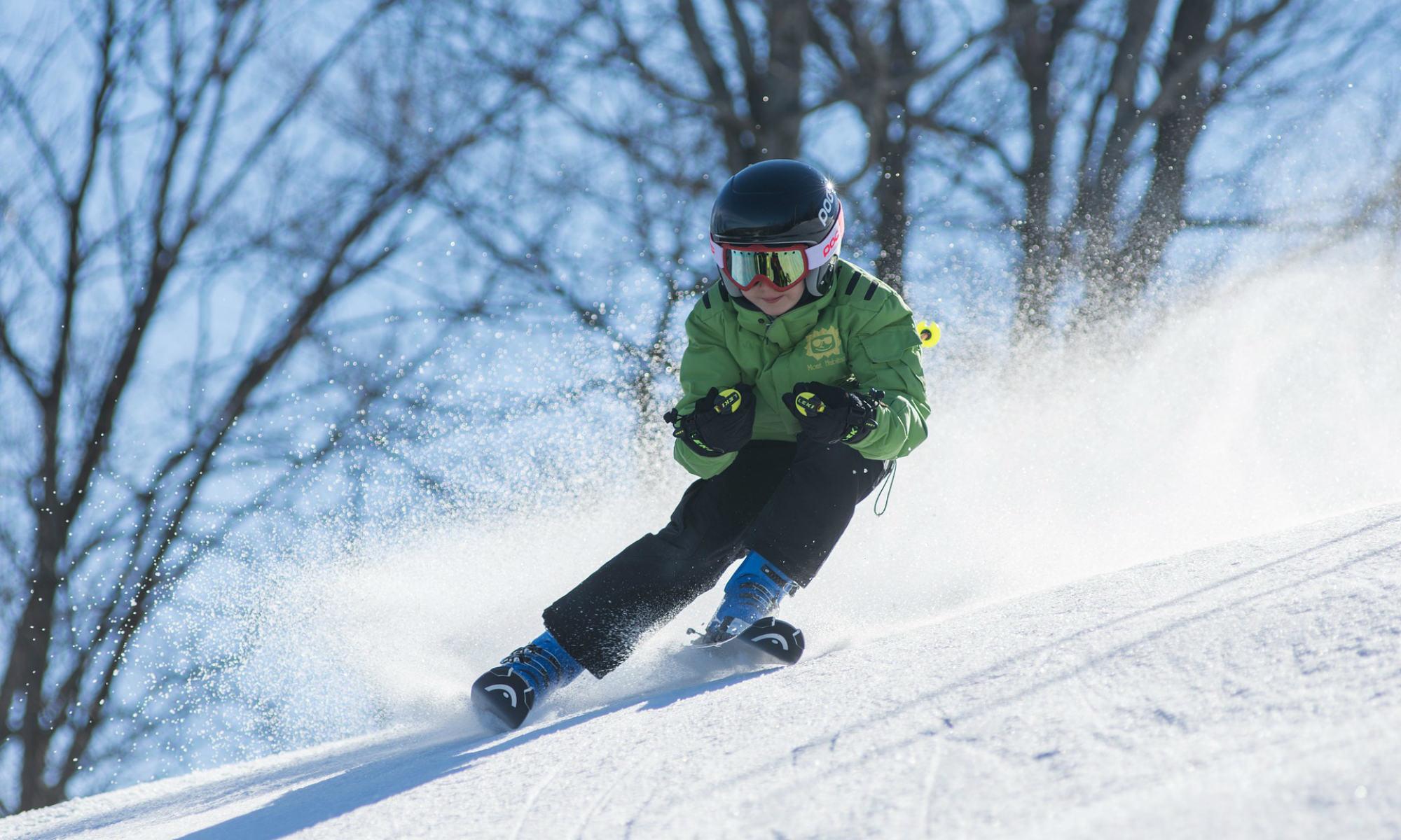 Ein 7-jähriges Kind beim Skifahren mit Parallelschwung.