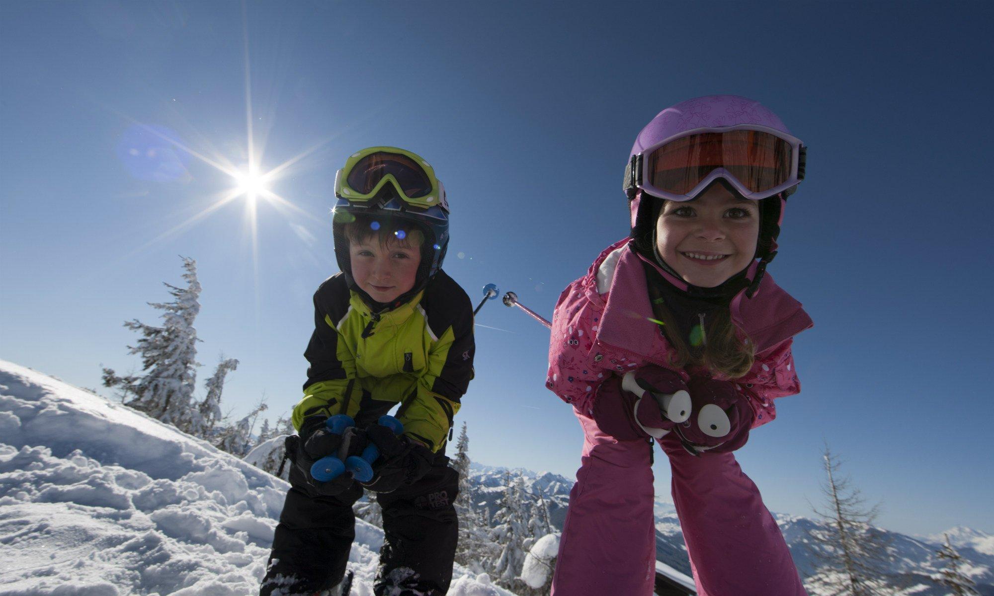 Zwei 6-jährige Kinder haben Spaß beim Skifahren.