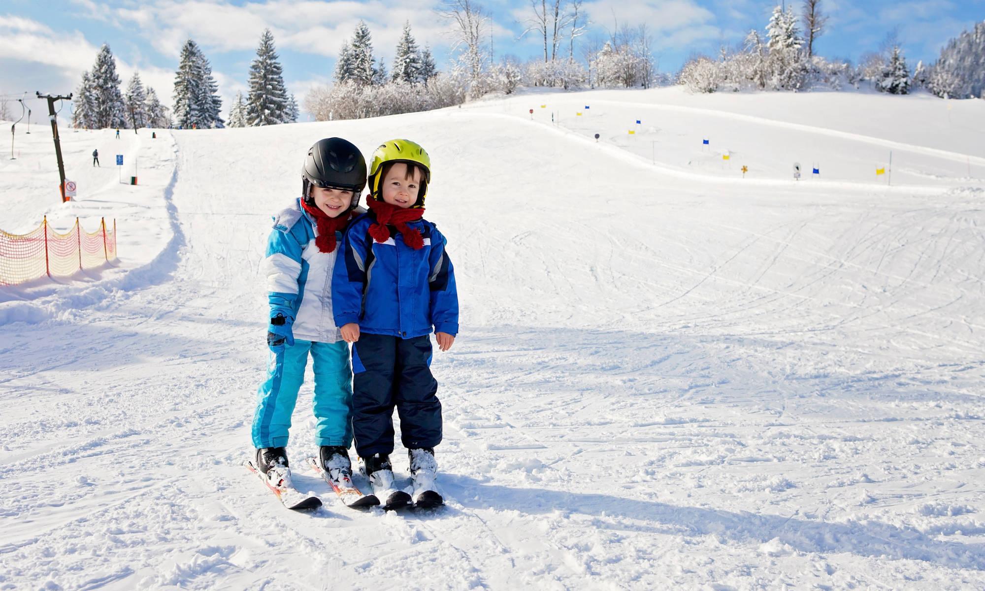 Zwei Kinder bei ihren ersten Skifahrer-Versuchen auf einer blauen Piste.